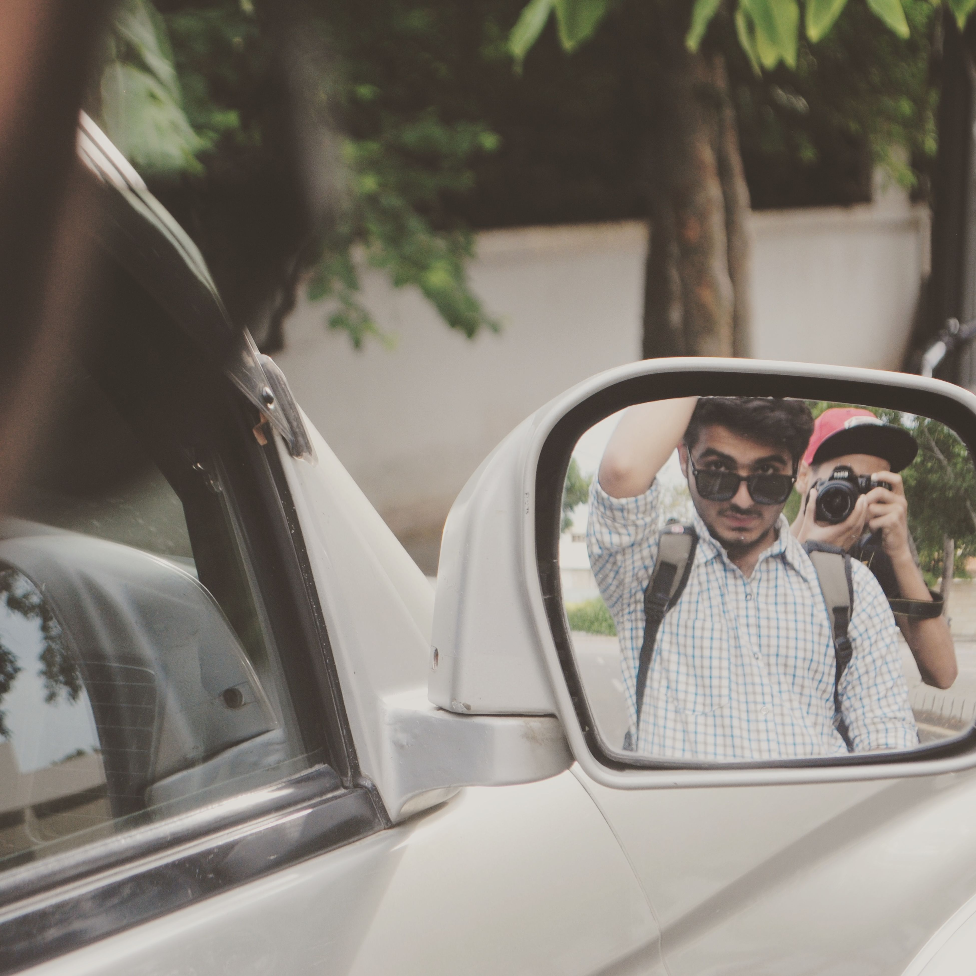 transportation, car, mode of transport, land vehicle, sunglasses, leisure activity, window, reflection, front view, young adult, looking at camera, day, focus on foreground, person