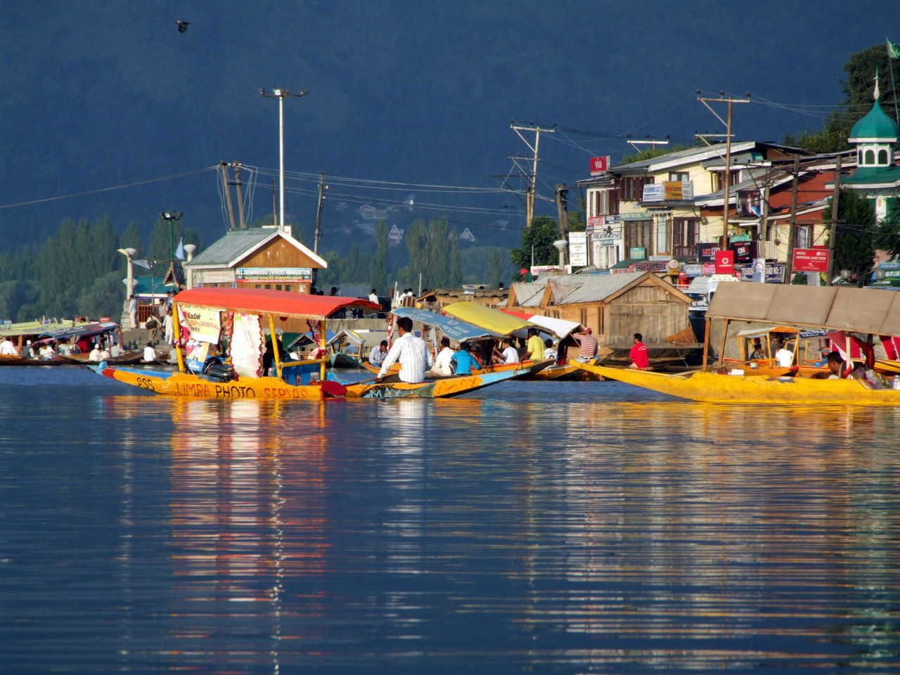 People In Boat On Lake By Houses