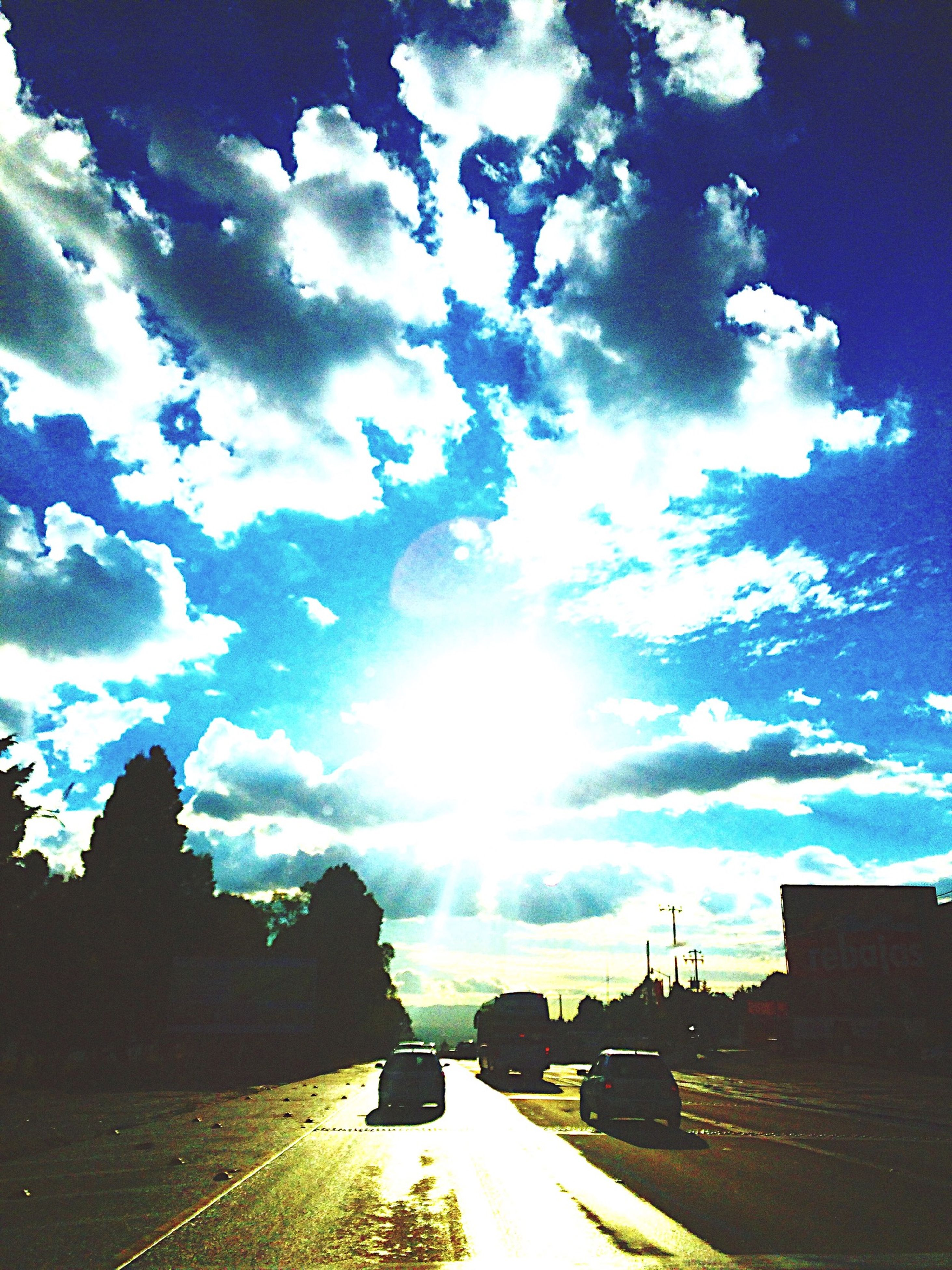 sky, cloud - sky, road, sun, transportation, car, sunlight, sunbeam, cloud, street, cloudy, nature, land vehicle, the way forward, lens flare, beauty in nature, scenics, outdoors, tranquility, blue