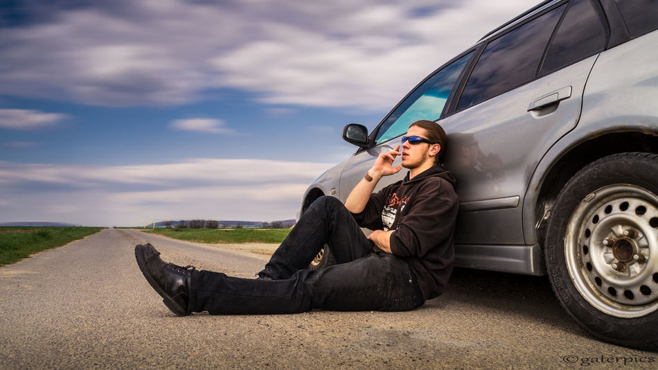 Adult Car Cloud - Sky Day EyeEmNewHere Land Vehicle Lifestyles One Person Outdoors People Real People Road Sitting Sky Stationary Tire Transportation Young Adult Young Man With Hair Tied To A Bun Leaning Against Car Enjoying A Cigarette Cigarette  Cigarette Time Freedom TCPM