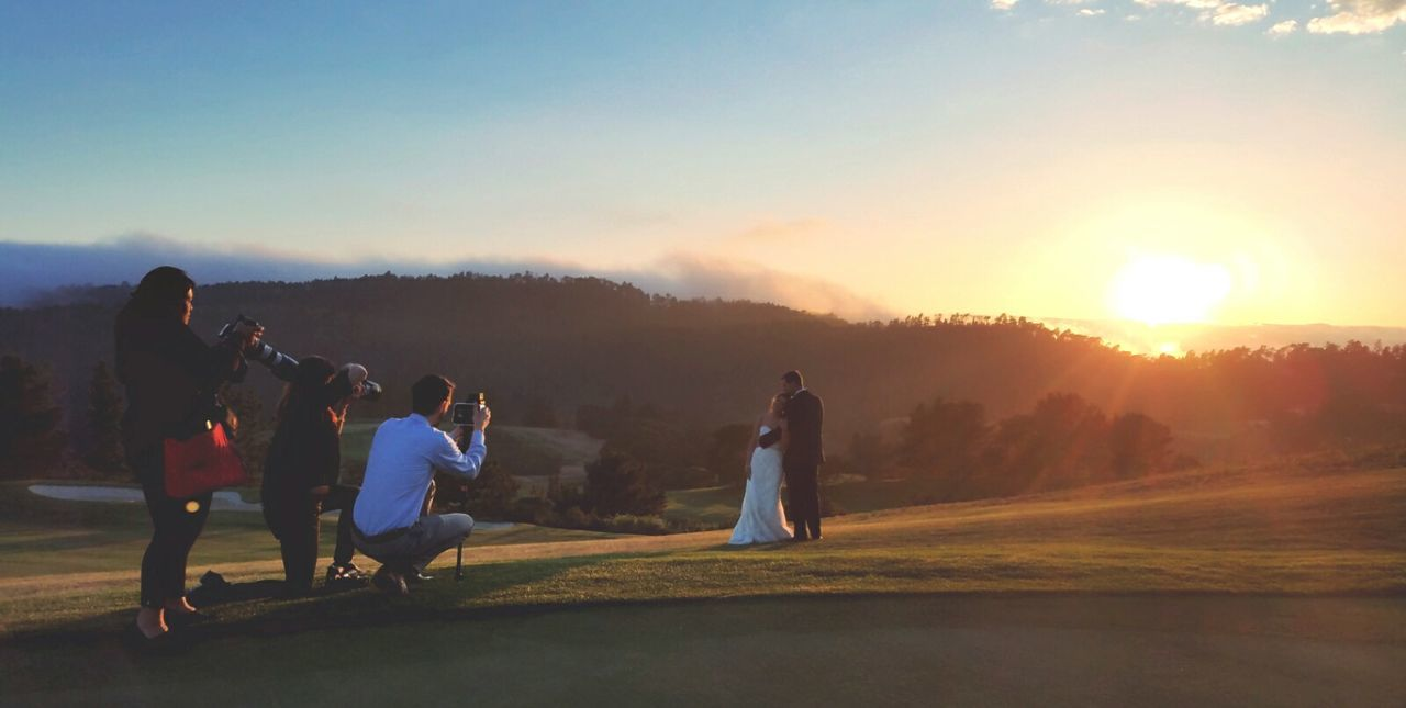 sunset, men, bride, togetherness, women, sunlight, sun, real people, wedding, leisure activity, full length, grass, life events, wedding dress, nature, standing, outdoors, bonding, bridegroom, sky, tree, friendship, groom, young adult, day, adult, people
