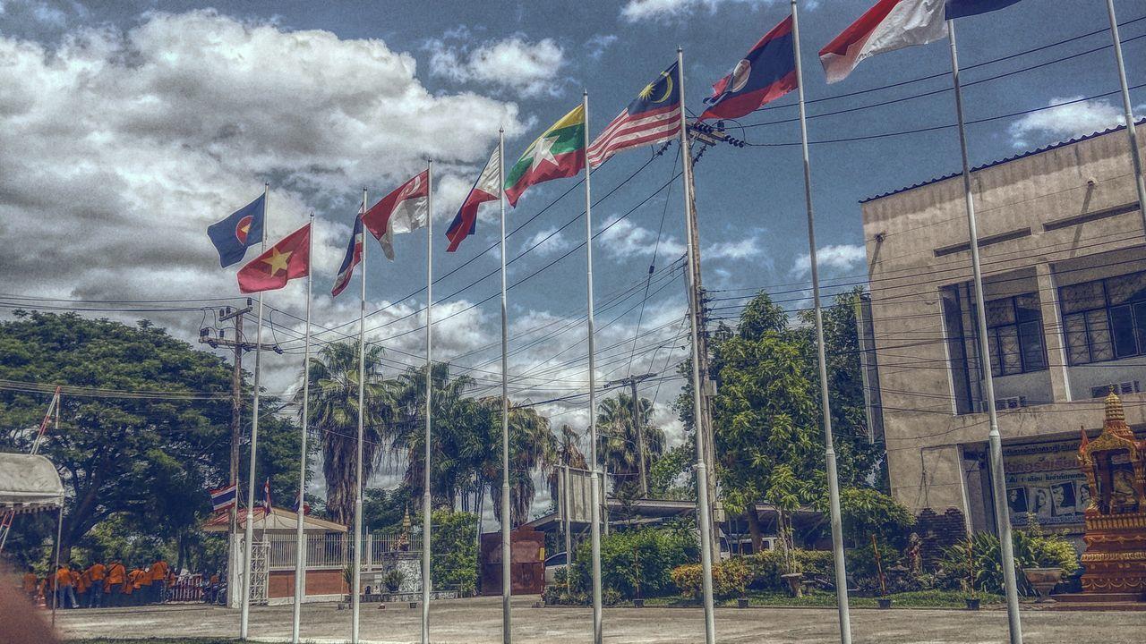 flag, patriotism, cloud - sky, sky, flag pole, day, outdoors, architecture, fluttering, building exterior, no people, tree, built structure, nature