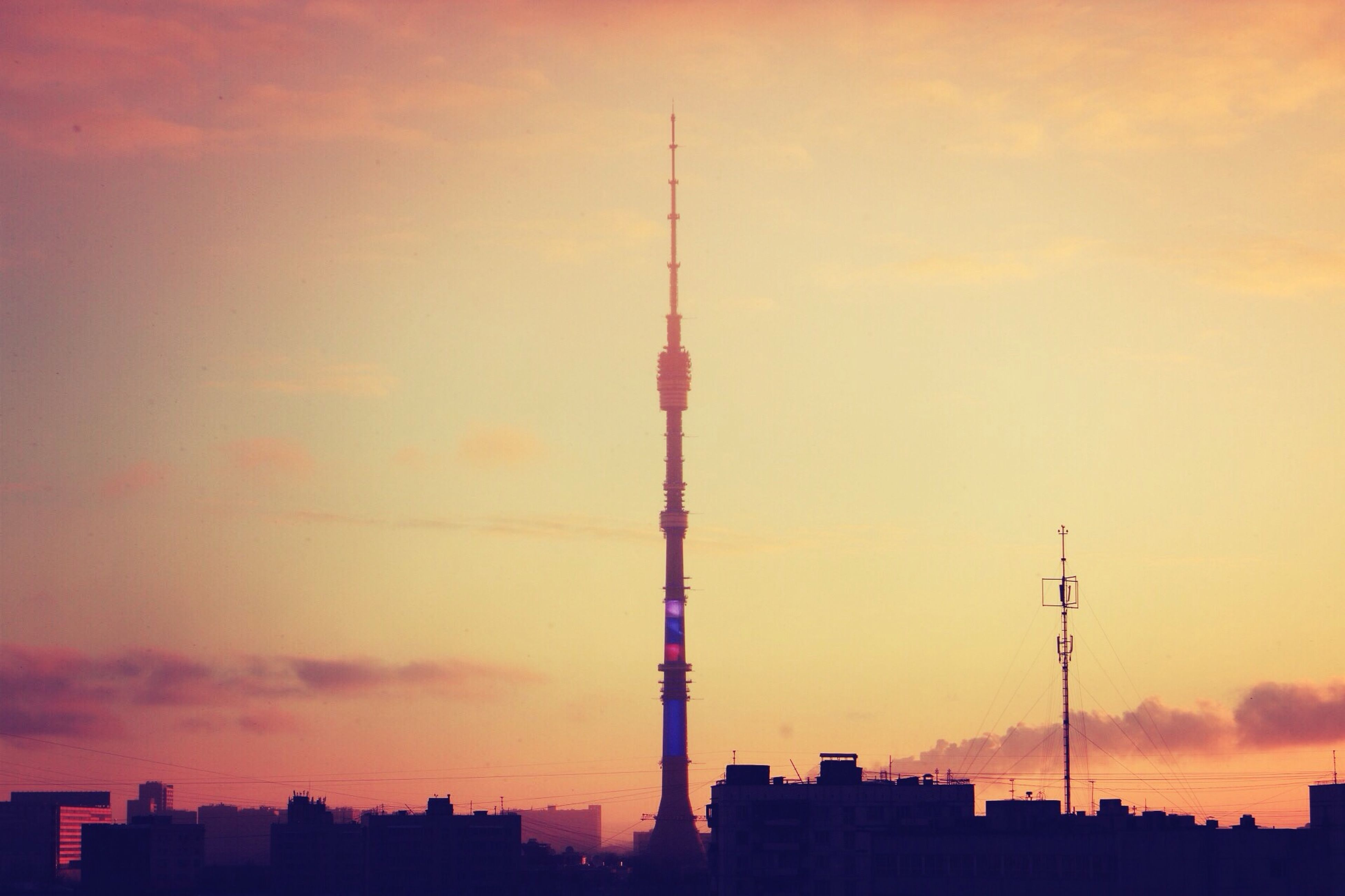 building exterior, architecture, sunset, built structure, tower, communications tower, tall - high, city, silhouette, sky, skyscraper, spire, orange color, communication, low angle view, cloud - sky, fernsehturm, capital cities, television tower, travel destinations