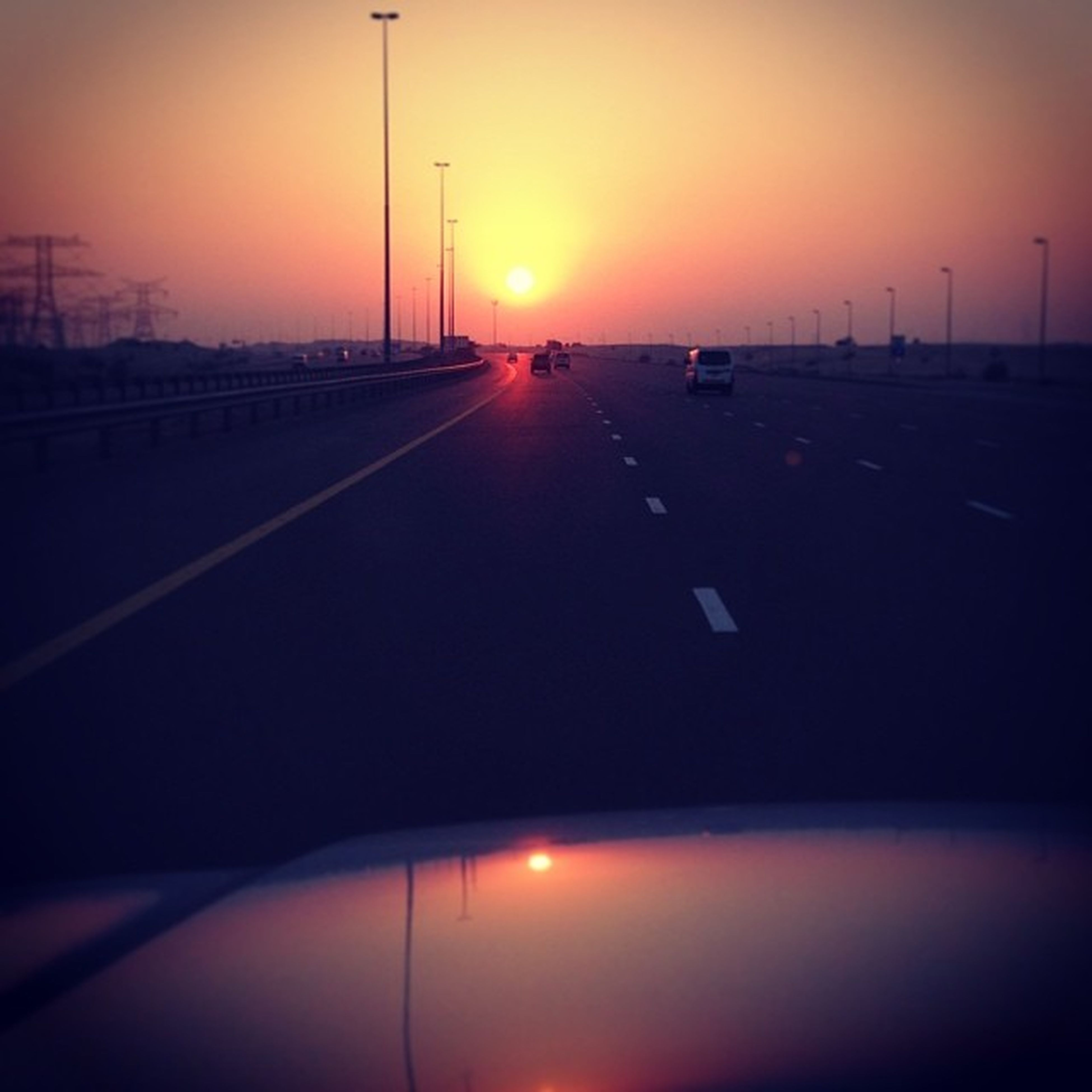 sunset, transportation, sun, orange color, mode of transport, silhouette, car, the way forward, road, sky, street light, diminishing perspective, land vehicle, sunlight, lens flare, travel, sunbeam, vanishing point, road marking, no people