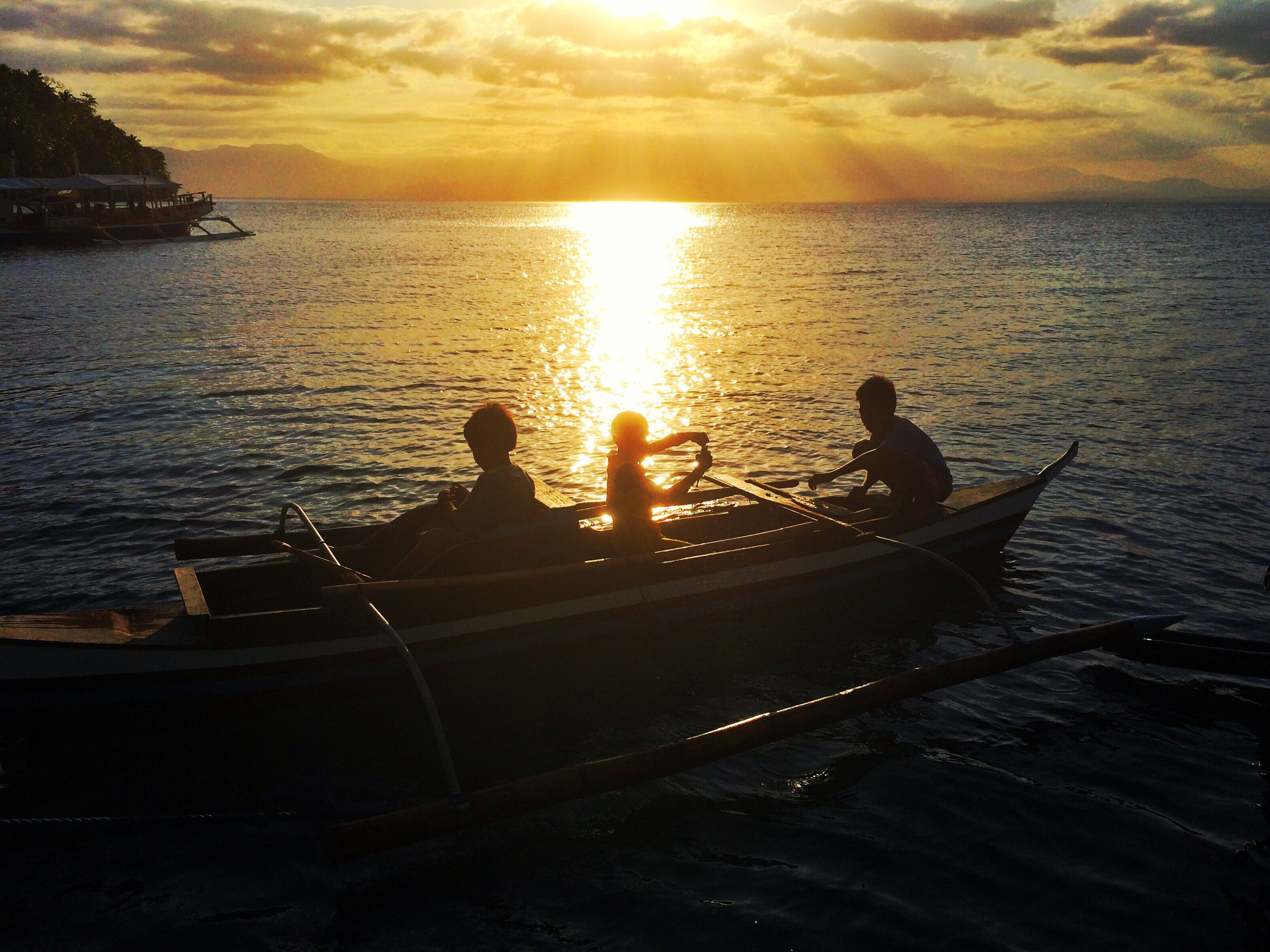 sunset, silhouette, nautical vessel, sea, sunlight, water, men, leisure activity, nature, beauty in nature, sky, real people, two people, outdoors, sun, vacations, cloud - sky, togetherness, friendship, adventure, only men, people, rowing, adult, day