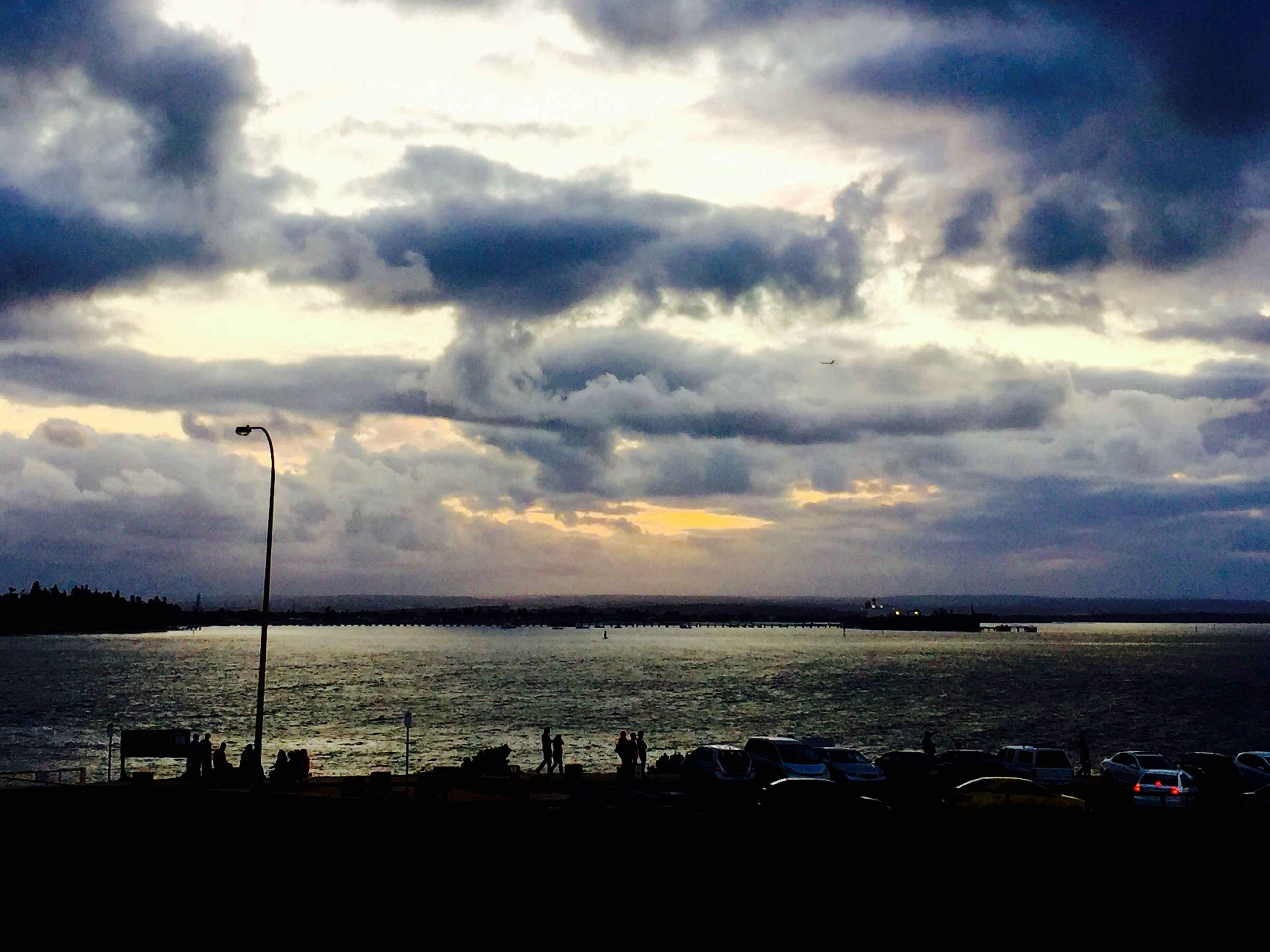 sky, cloud - sky, cloudy, tranquility, scenics, tranquil scene, beauty in nature, sunset, water, silhouette, cloud, nature, weather, dusk, street light, idyllic, landscape, sea, outdoors, overcast