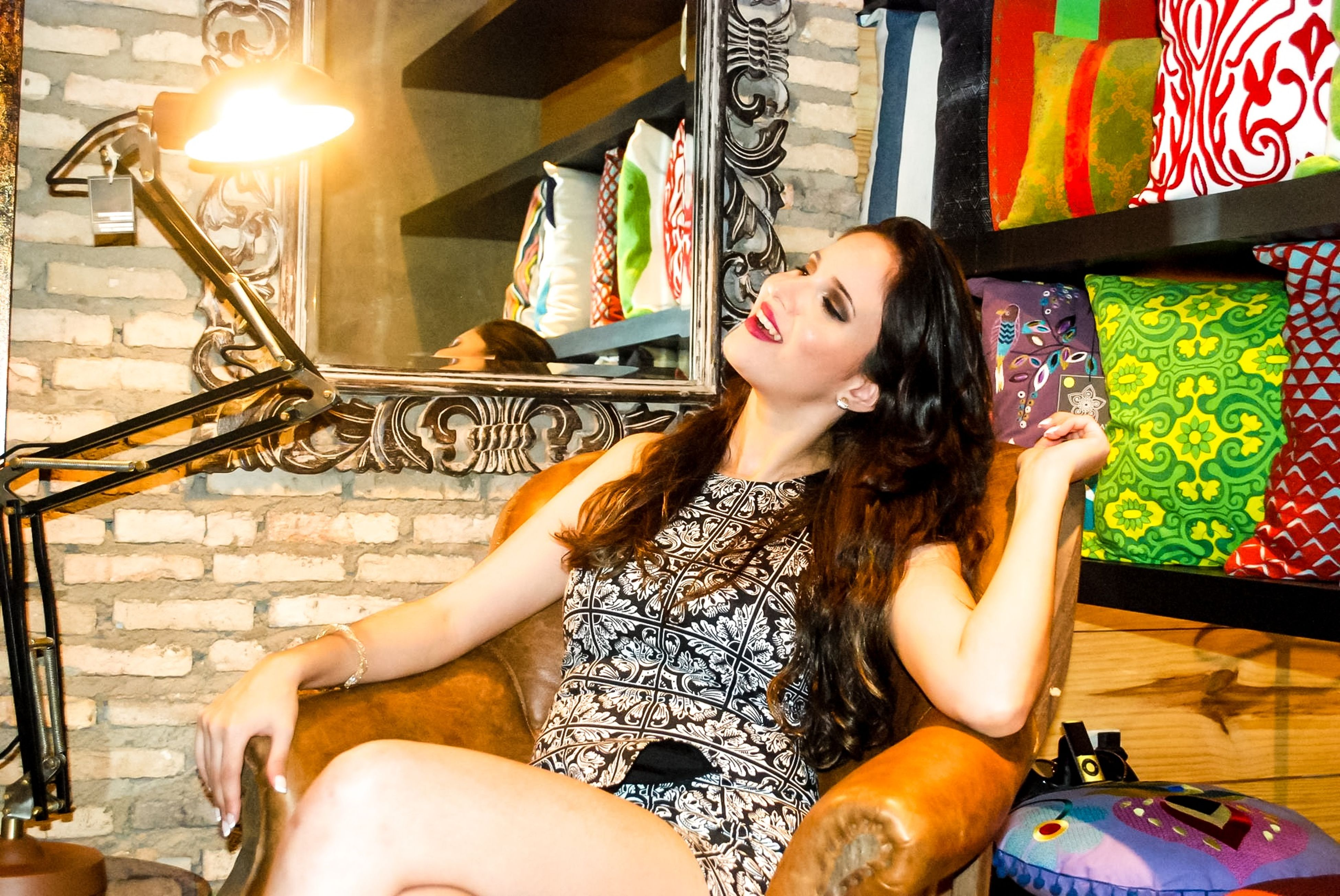 indoors, lifestyles, person, casual clothing, young adult, leisure activity, young women, sitting, three quarter length, illuminated, retail, front view, looking at camera, smiling, waist up, happiness