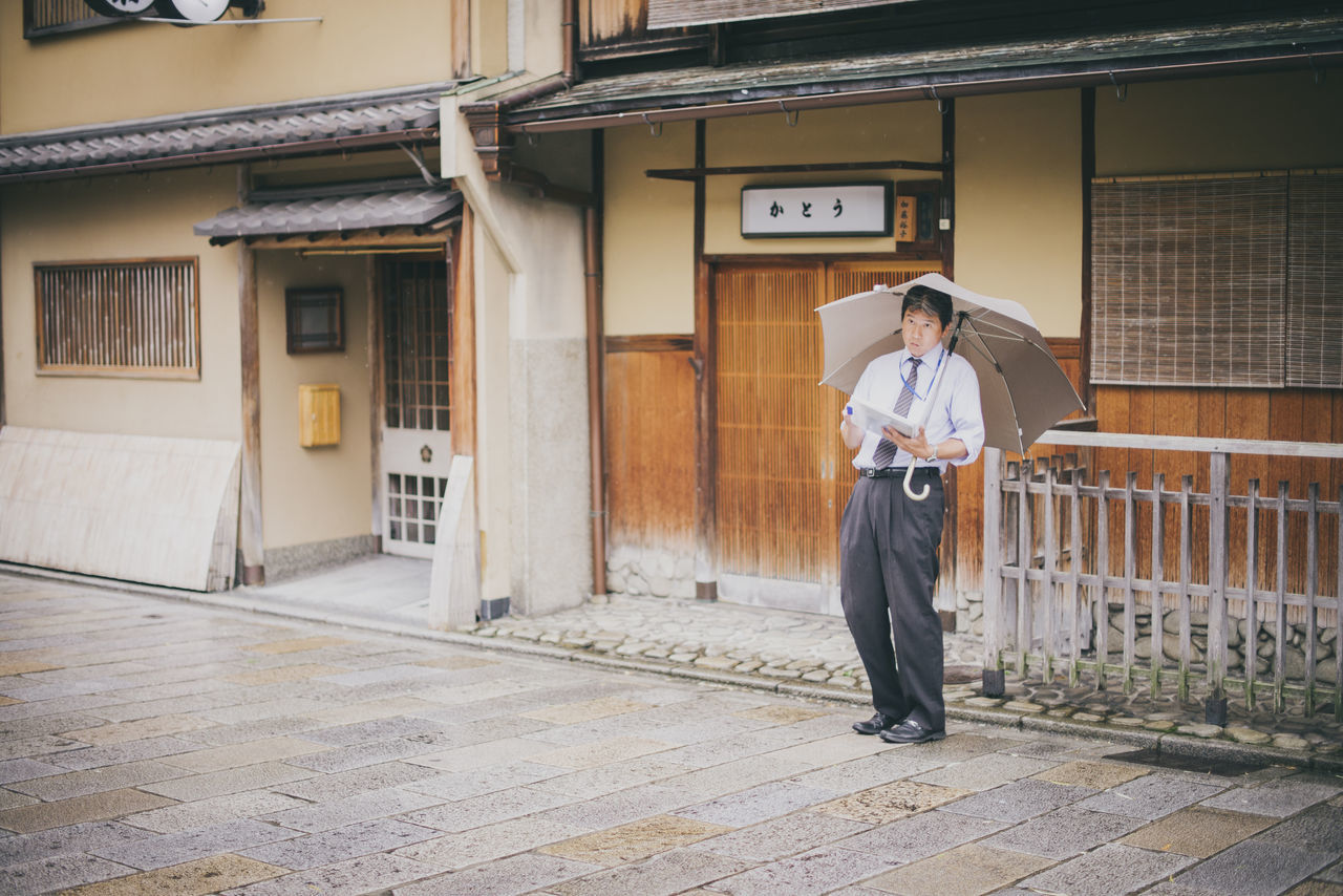 Doing checkups in Gion, Kyoto, Japan. Adult Adults Only Building Exterior Candid Classic Culture Day Full Length Gion Japan Japanese  Japanese Style Men Outdoors People Portable Information Device Rain Rainy Days Smart Phone Street Technology Traditional Travel Destinations Umbrella