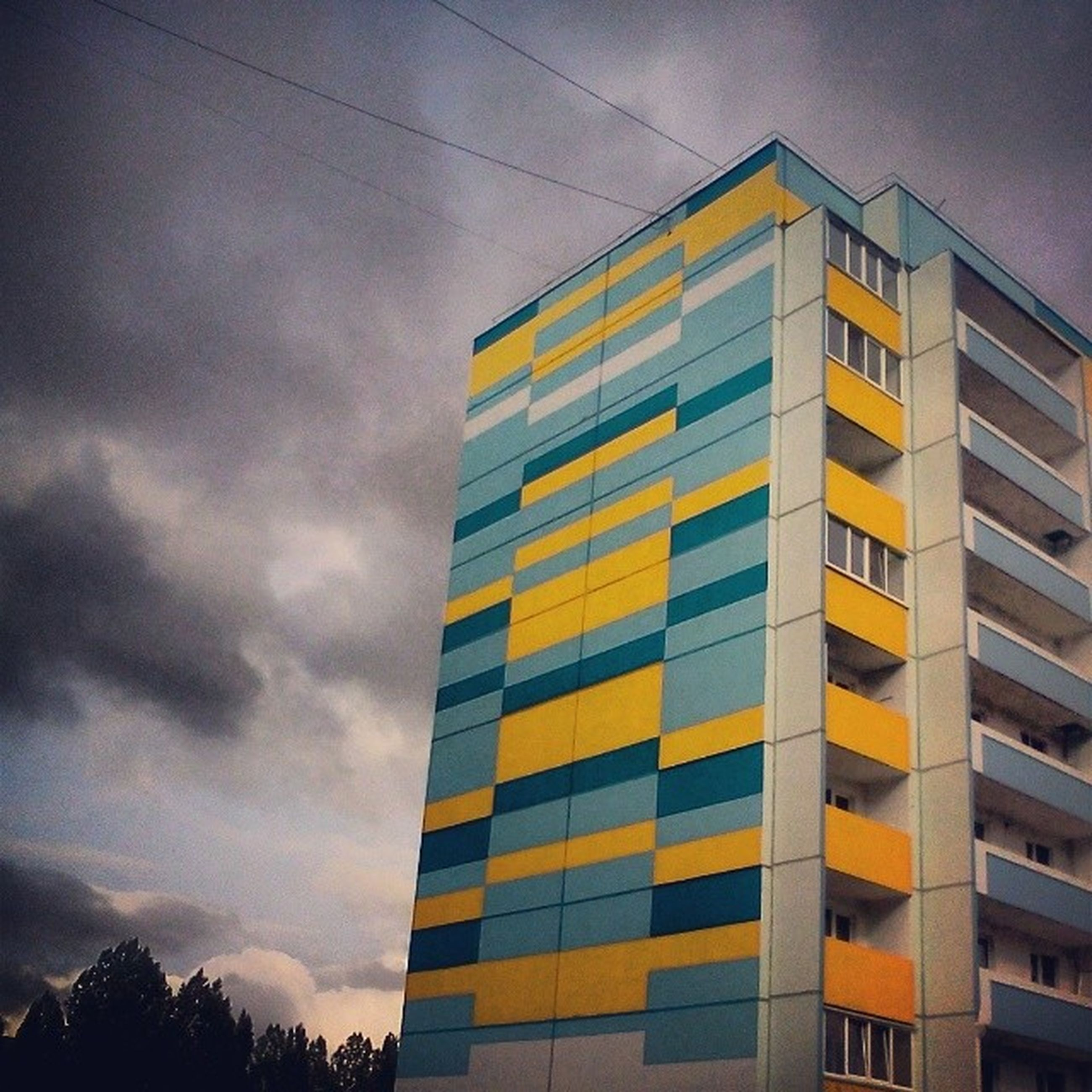 architecture, building exterior, built structure, low angle view, sky, window, building, city, cloud - sky, residential building, residential structure, cloud, no people, cloudy, outdoors, apartment, modern, day, sunset, glass - material