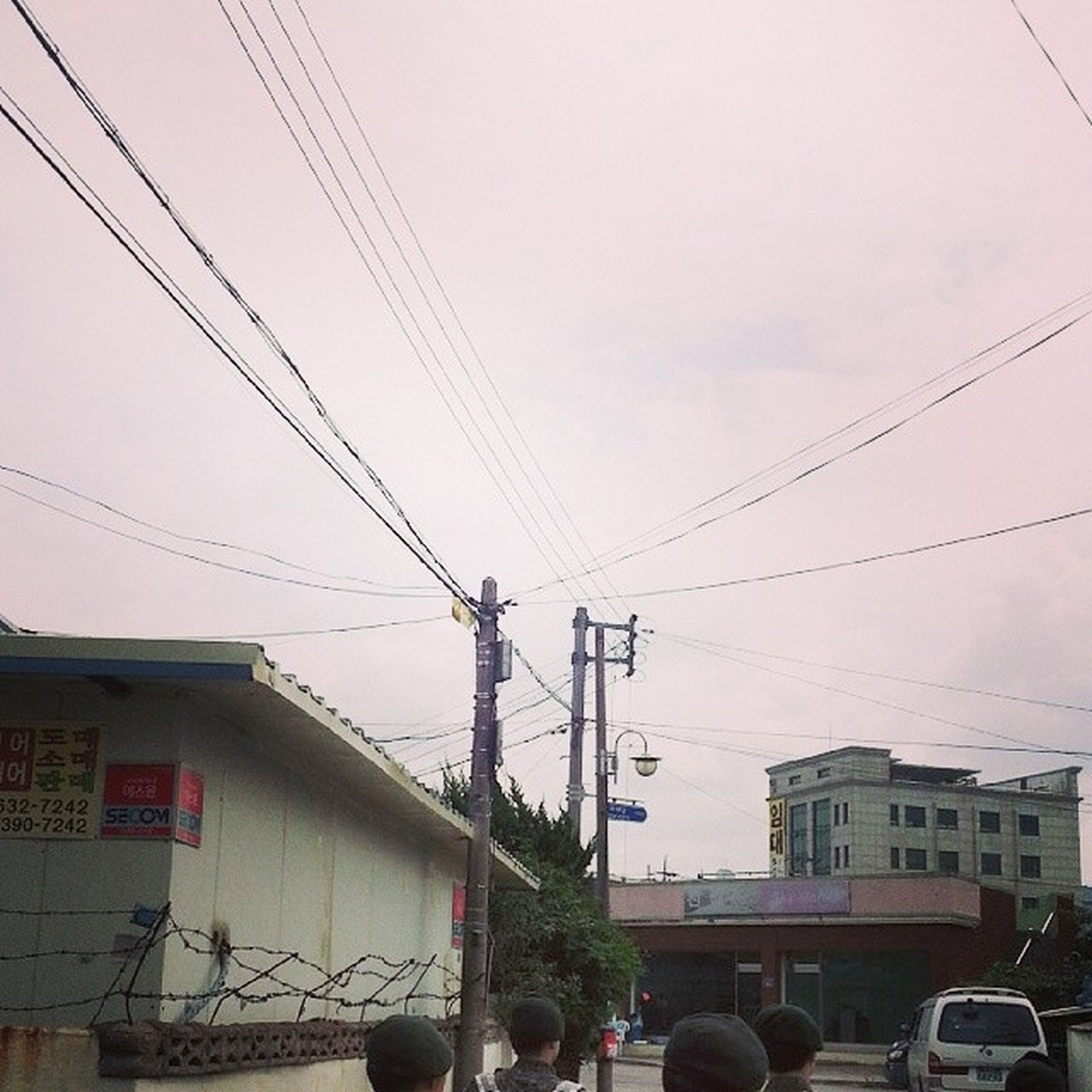 power line, electricity pylon, cable, building exterior, transportation, architecture, power supply, built structure, electricity, car, mode of transport, street, land vehicle, city, power cable, sky, connection, fuel and power generation, residential structure, residential building