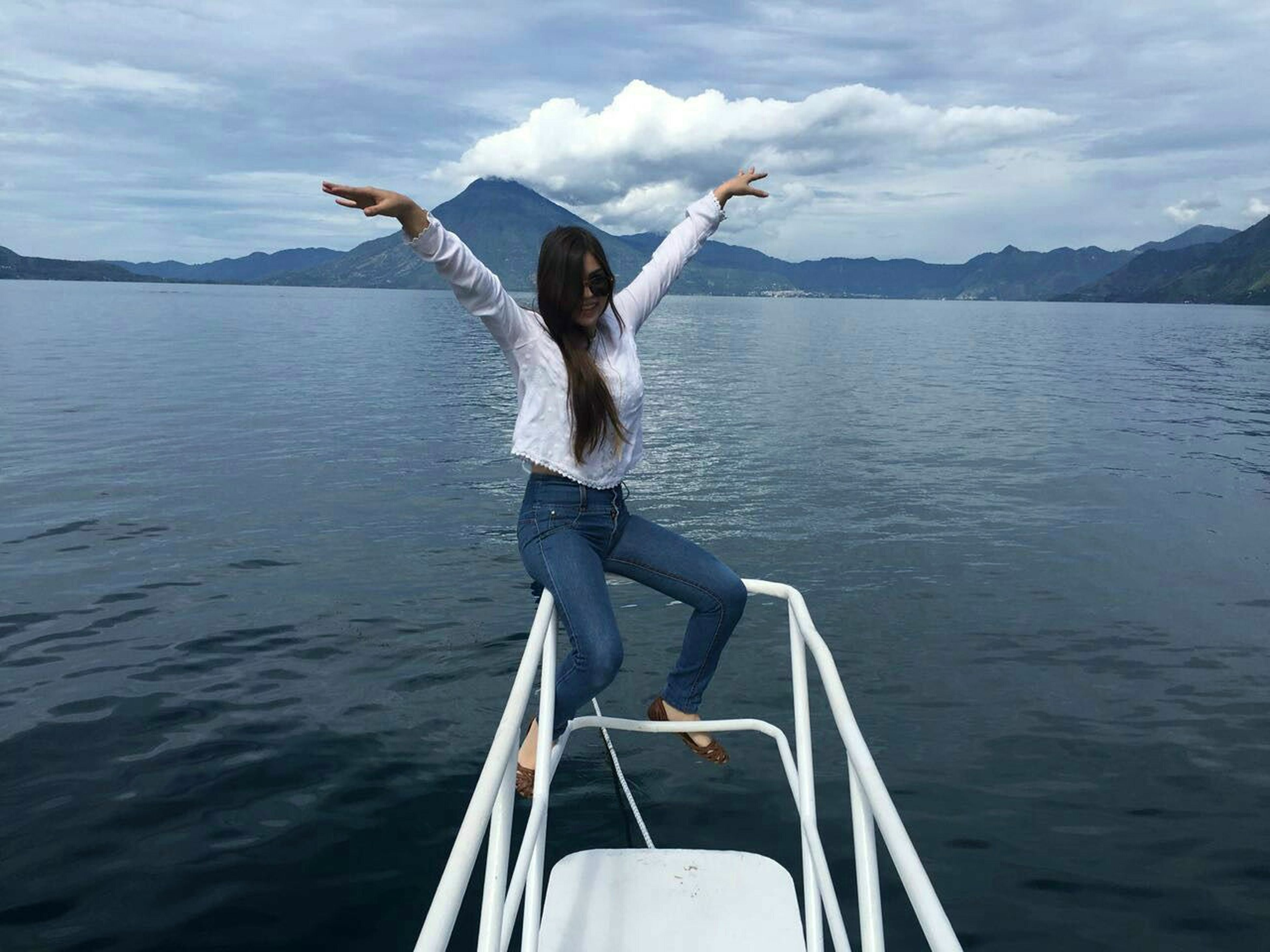 water, sky, nautical vessel, boat, mountain, mode of transport, cloud - sky, lifestyles, leisure activity, cloud, rippled, nature, beauty in nature, scenics, tranquility, jumping, outdoors, tranquil scene, sailing, mountain range, day, cloudy, vacations, part of, idyllic