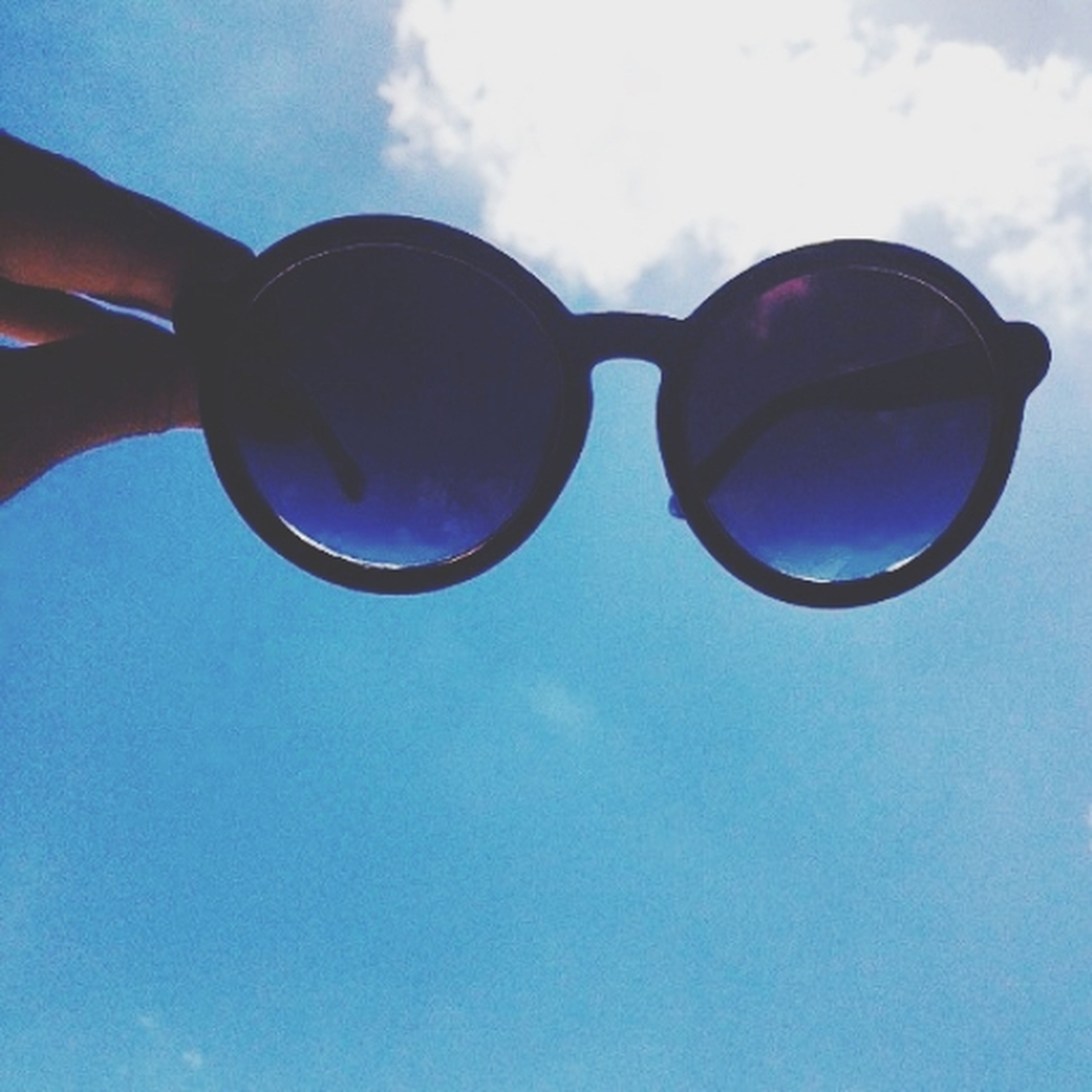 blue, sky, sunglasses, low angle view, reflection, close-up, part of, leisure activity, transparent, cloud - sky, day, lifestyles, glass - material, mid-air, balloon, cloud, outdoors, sunlight