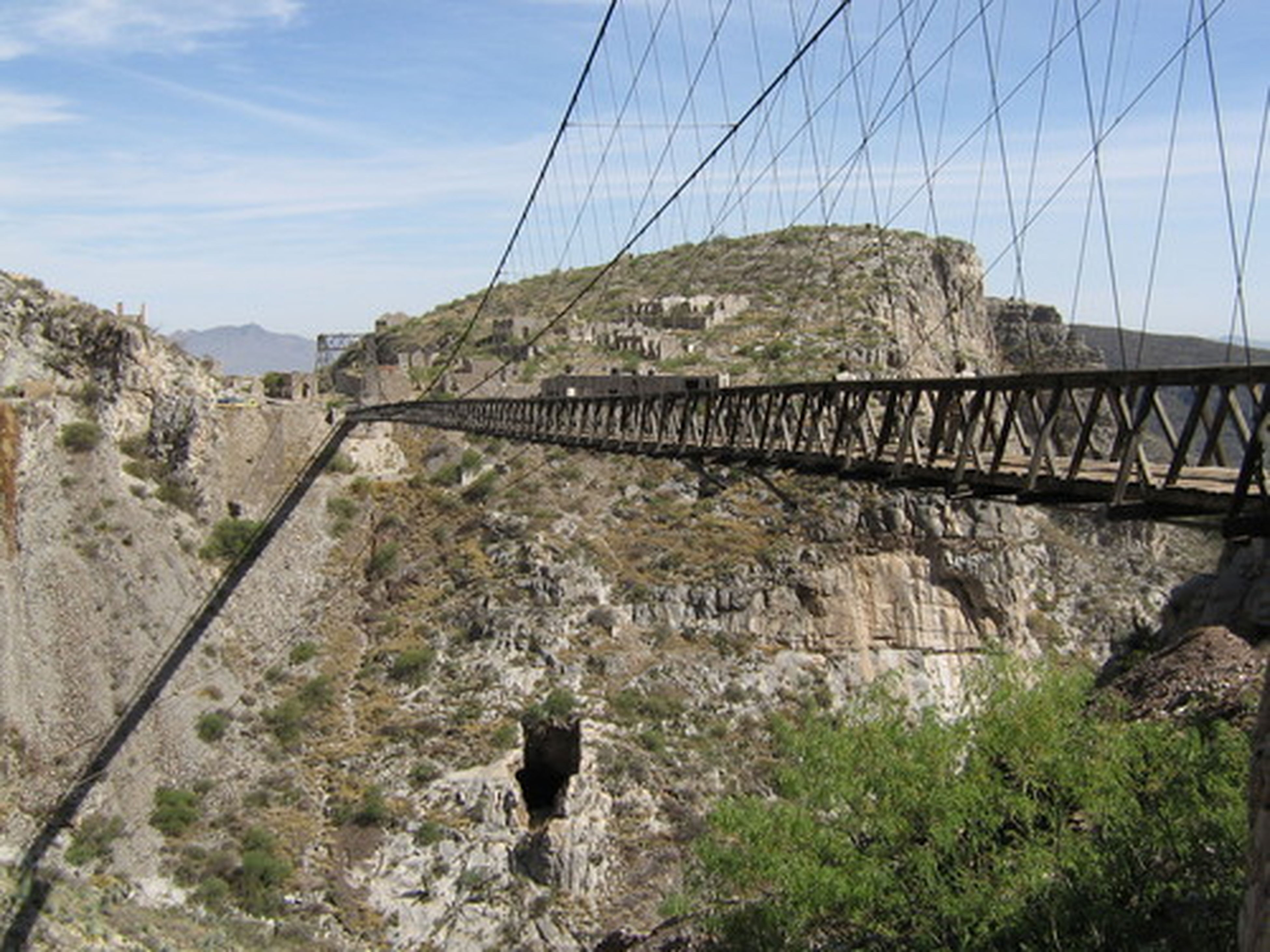 connection, built structure, architecture, mountain, bridge - man made structure, sky, rock - object, low angle view, engineering, transportation, electricity pylon, cable, power line, suspension bridge, day, bridge, rock formation, mountain range, landscape, no people