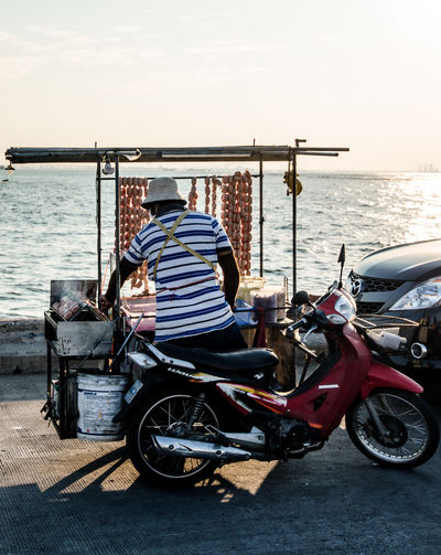 Motorcycle with Thai street food (Grilled sausage) Food Food Truck Land Vehicle Lifestyles Man Men Mode Of Transport Motorcycle Motorcycle Occupation Parked Preparation  Preparing Food Road Seaside Sell Sitting Street Food Transportation