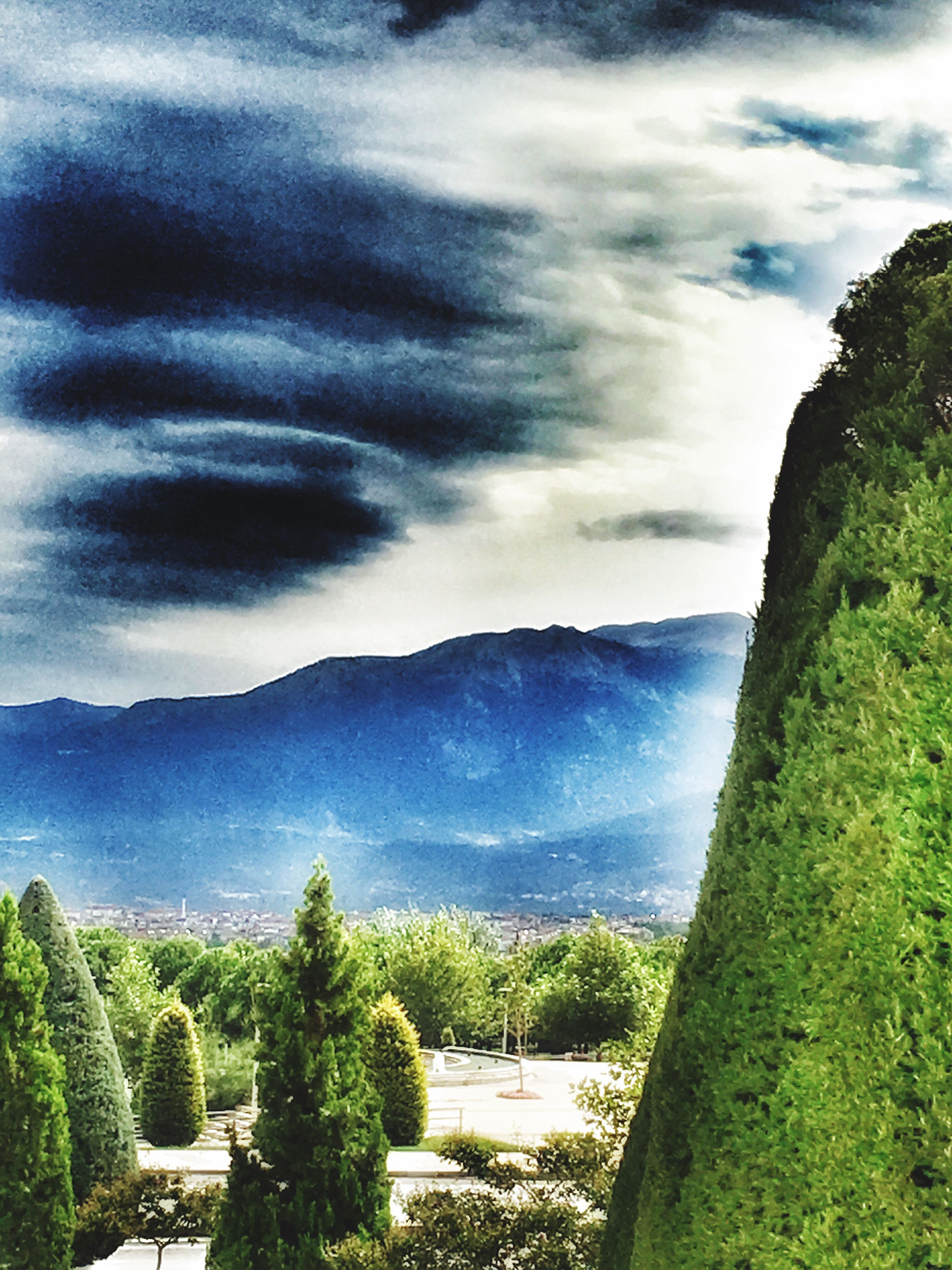 mountain, scenics, tranquil scene, tree, tranquility, beauty in nature, cloud - sky, growth, sky, tourism, nature, plant, non-urban scene, travel destinations, sea, water, outdoors, majestic, mountain range, cloudy, day, solitude, remote, no people, green color, in front of, storm cloud, physical geography