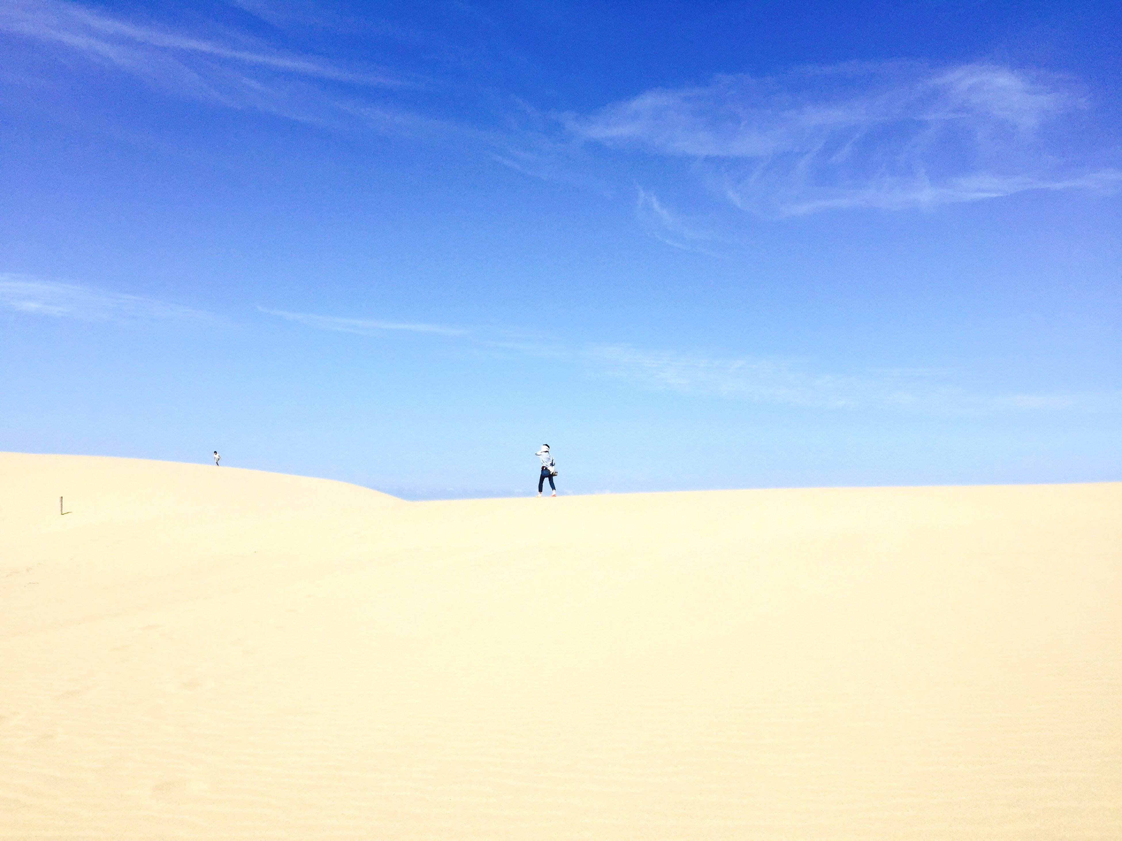 sand, tranquil scene, tranquility, leisure activity, sky, lifestyles, men, scenics, landscape, unrecognizable person, beauty in nature, nature, desert, blue, beach, sand dune, remote, tourist