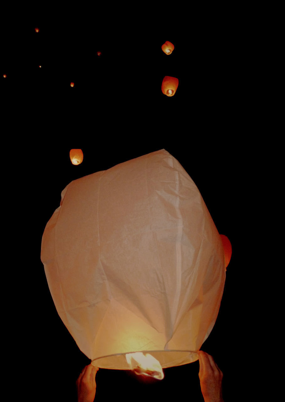 Cropped Hands Flying Paper Lantern At Night