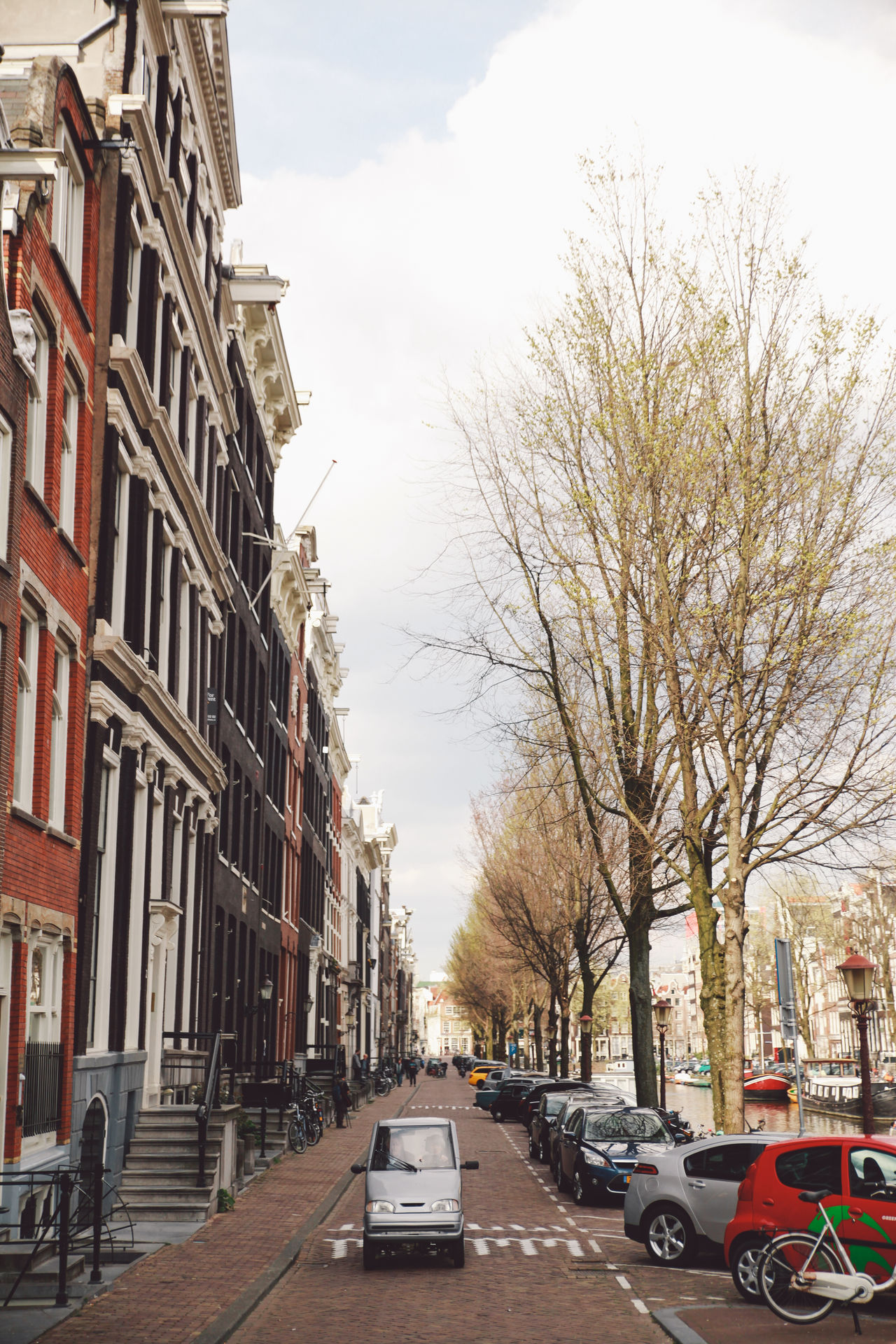 2016 April Architecture Bare Tree Building Built Structure MeinAutomoment Need For Speed City Street Electric Car In A Row Land Vehicle Mode Of Transport Outdoors Residential Building Road Small Car Spring The Way Forward Transportation Tree Vanishing Point Your Amsterdam Telling Stories Differently The Street Photographer - 2016 EyeEm Awards