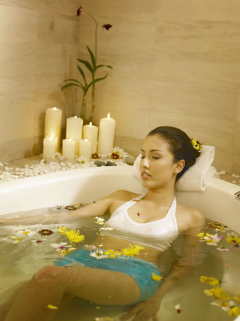 beautiful woman enjoying big jacuzzi Bath Candle Eyes Closed  Health And Beauty Hygiene Recreation  Relaxing Tranquility Wellness Aroma Therapy Bathroom Beuty Body Care Female Flower Hotel Jacuzzi  Leisure Activity Luxury Pampering Relax Satisfaction Spa Water Wellbeing