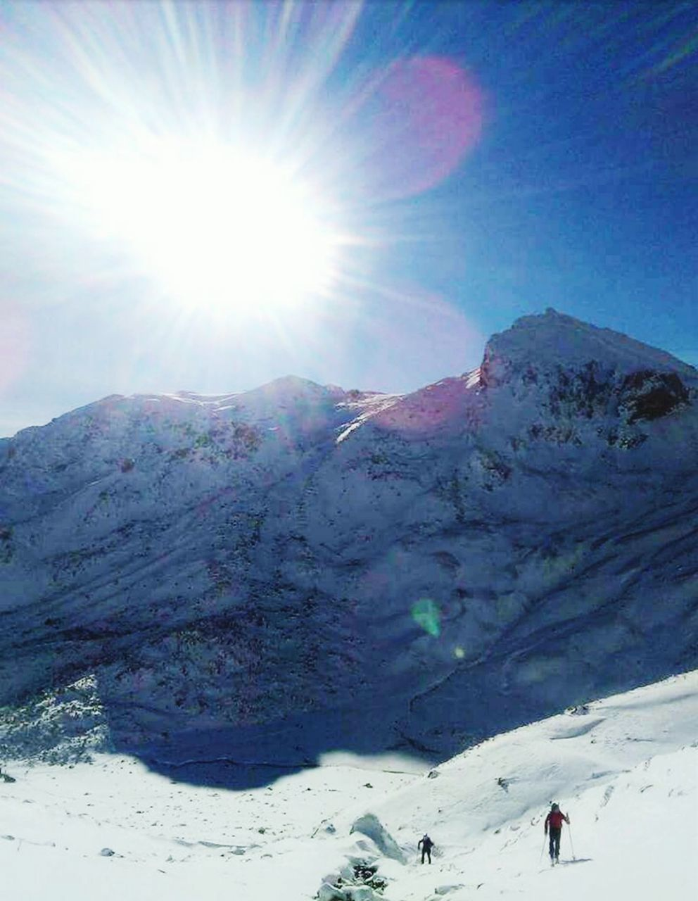 sunlight, snow, winter, lens flare, sun, mountain, nature, sunbeam, cold temperature, beauty in nature, scenics, tranquility, leisure activity, adventure, real people, vacations, weather, day, idyllic, tranquil scene, landscape, outdoors, snowcapped mountain, physical geography, sky, hiking, ski holiday, mountain range