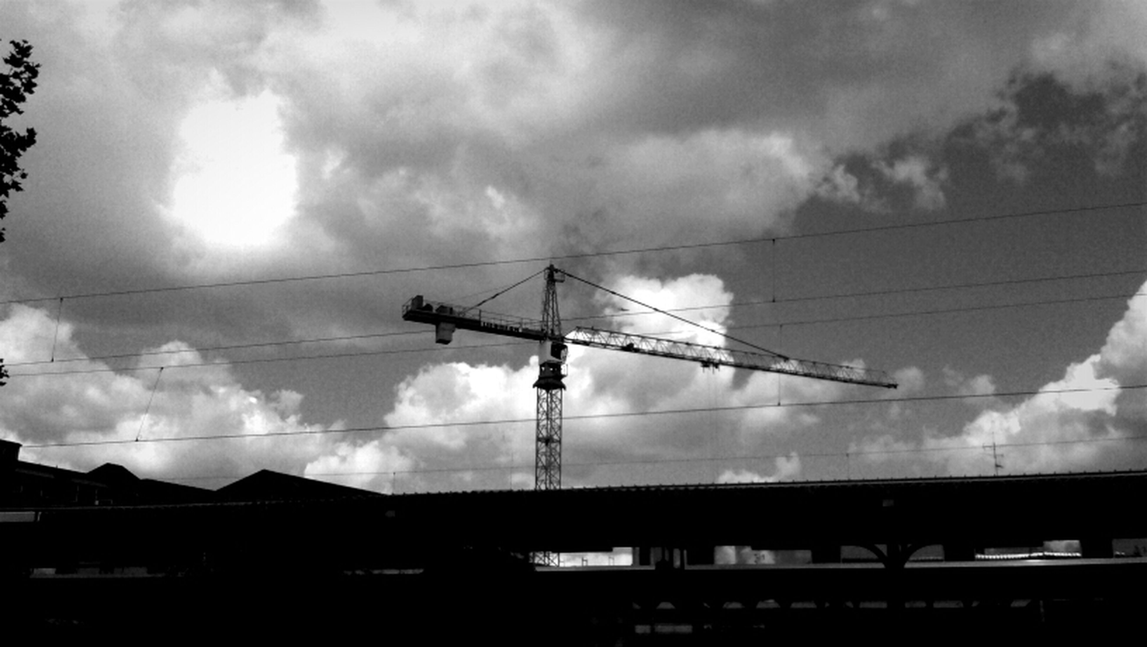 sky, low angle view, cloud - sky, connection, silhouette, cloudy, power line, electricity pylon, electricity, power supply, built structure, cable, cloud, fuel and power generation, technology, architecture, weather, crane - construction machinery, dusk, sunset