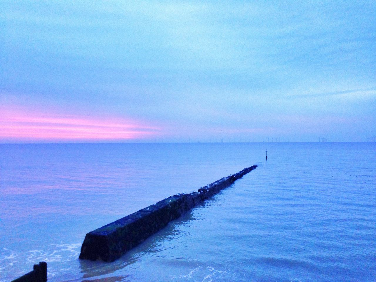 Scenic View Of Sea With Groyne During Sunset
