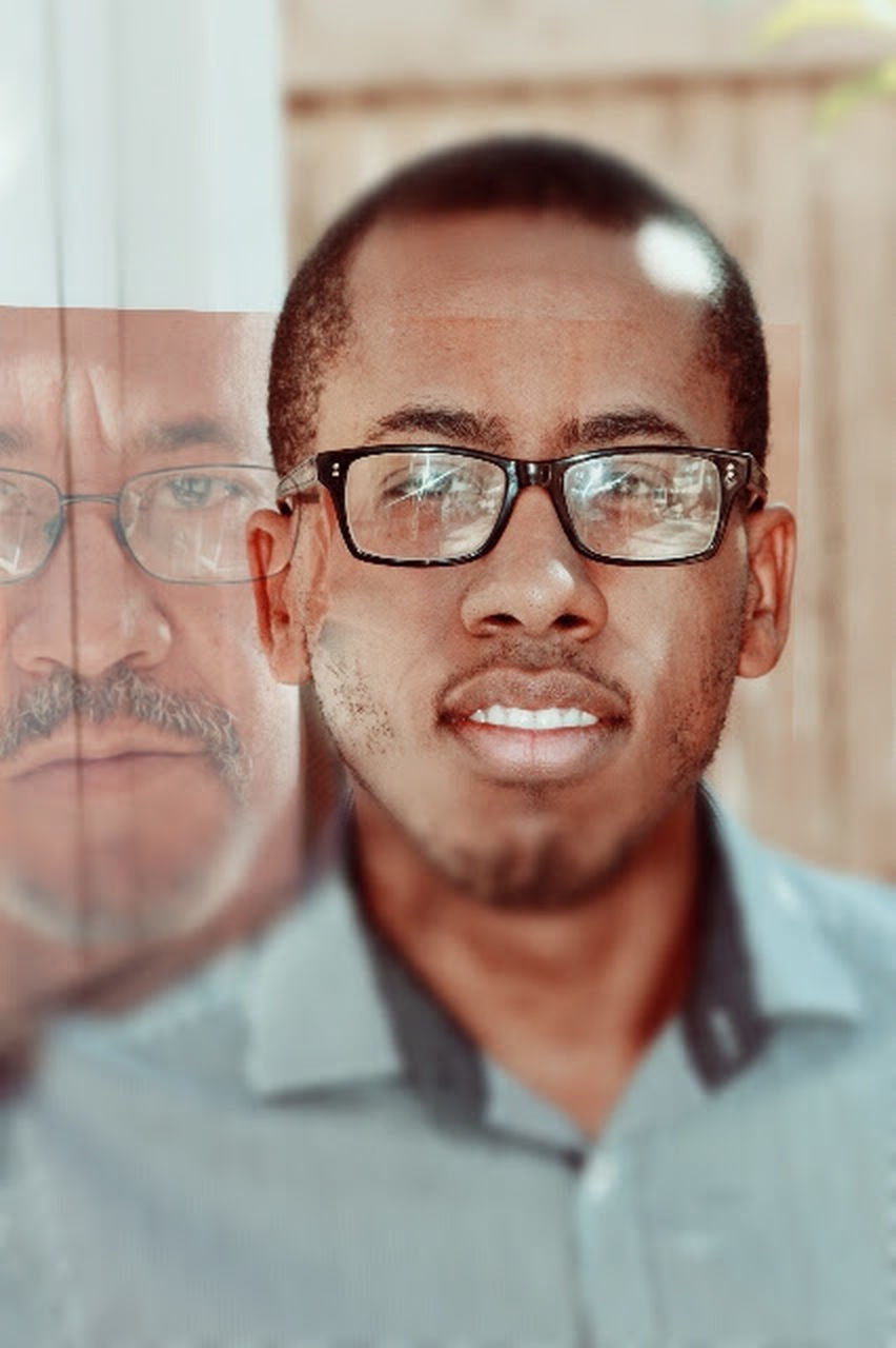 eyeglasses, looking at camera, one man only, portrait, only men, adults only, headshot, indoors, adult, front view, human body part, one person, human face, men, mature adult, close-up, smiling, people, day, human eye, young adult