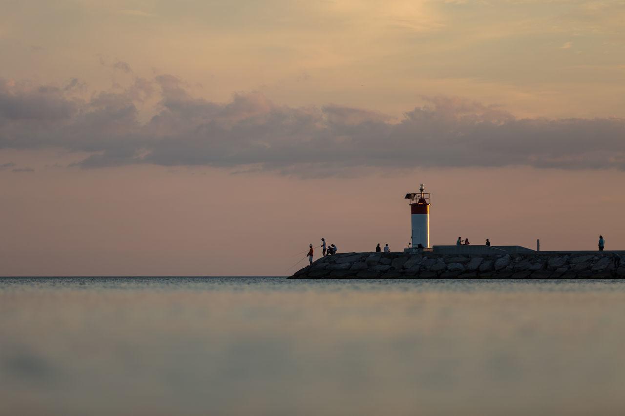 Lighthouse On Calm Sea At Sunset