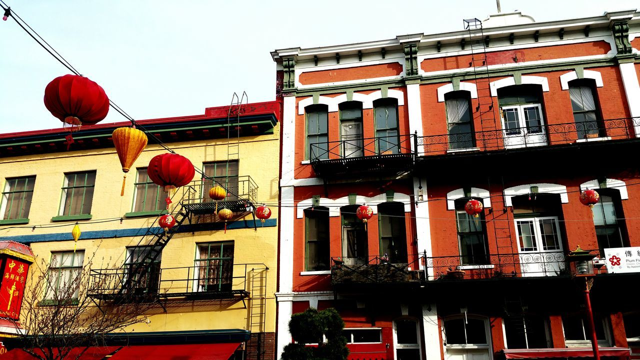 architecture, building exterior, built structure, chinese lantern, lantern, red, hanging, lighting equipment, low angle view, house, window, cultures, no people, outdoors, celebration, paper lantern, chinese lantern festival, residential building, day, chinese new year, city, sky