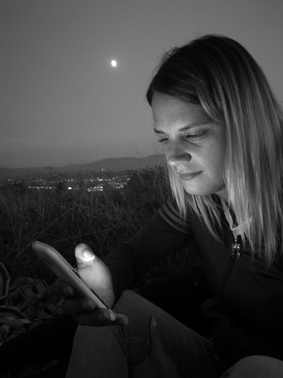 real people, one person, sitting, moon, leisure activity, lifestyles, young women, night, young adult, illuminated, outdoors, nature, close-up, blond hair, sky