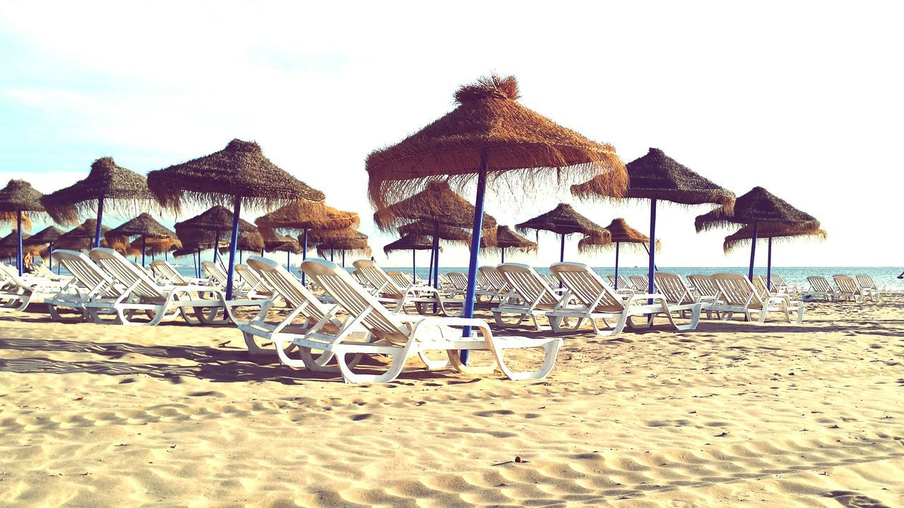Thatched Roofs And Lounge Chairs At Beach Against Sky