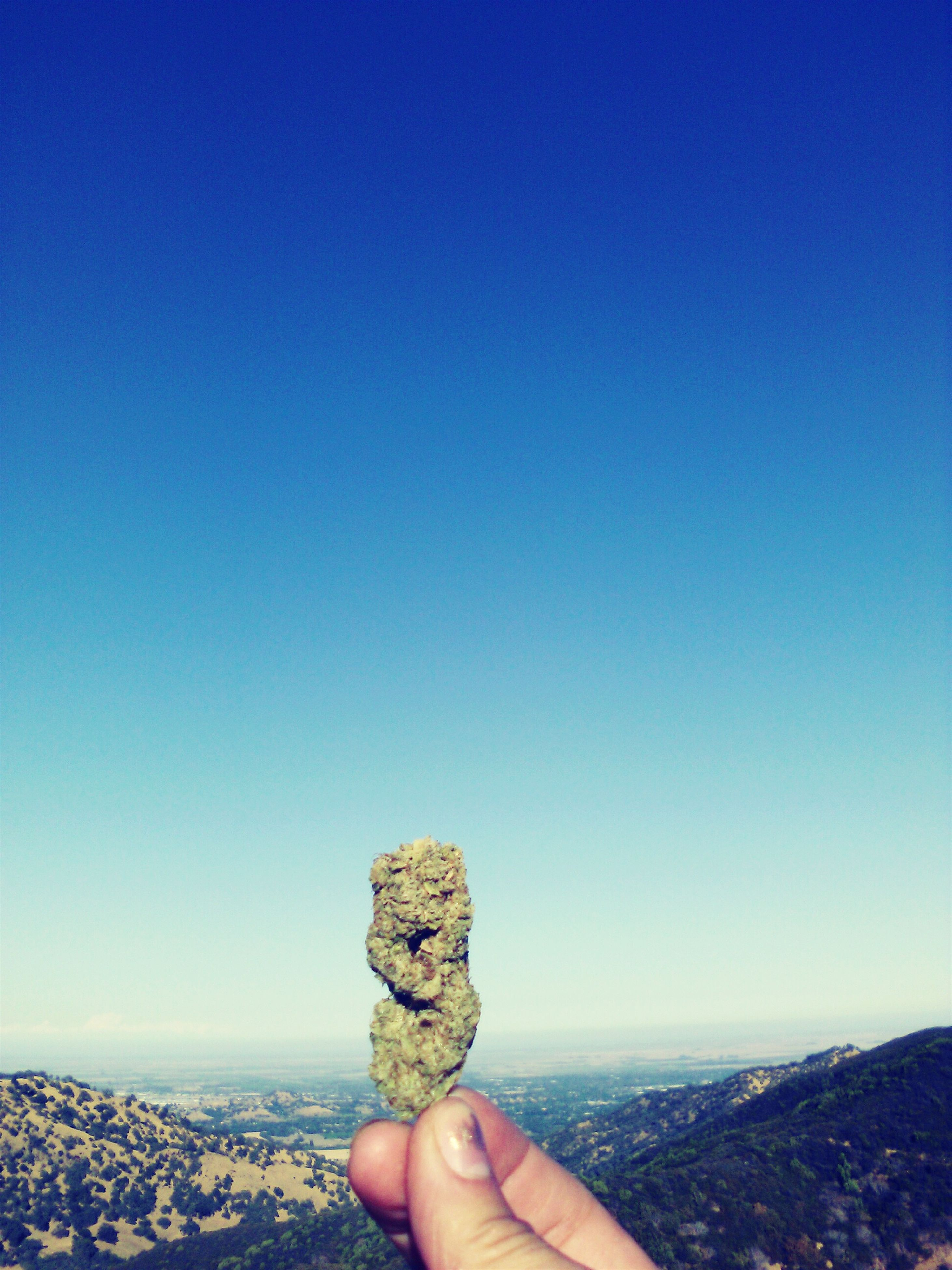 copy space, clear sky, personal perspective, person, blue, part of, lifestyles, leisure activity, cropped, rock - object, holding, human finger, unrecognizable person, day, men, nature, outdoors