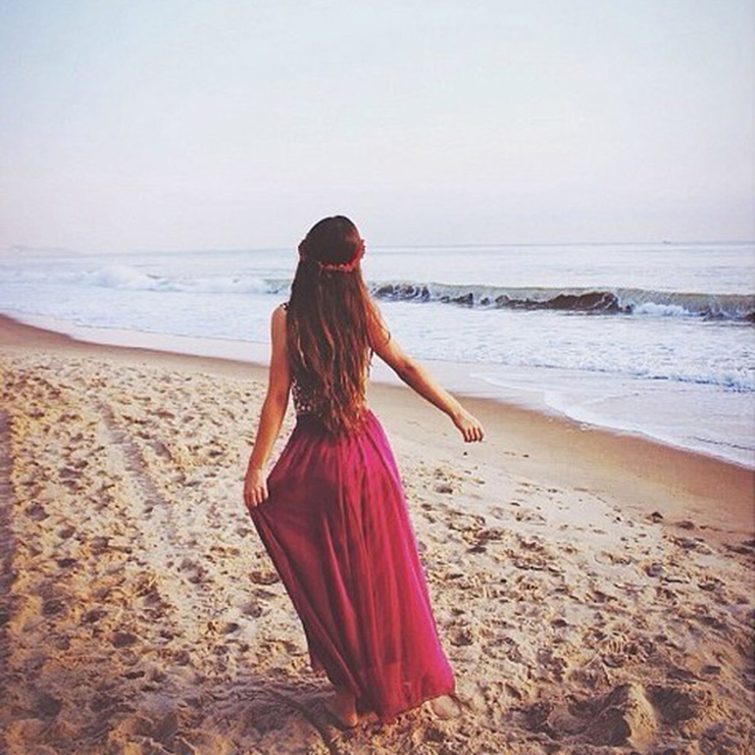 beach, sea, horizon over water, shore, water, standing, sand, clear sky, tranquil scene, vacations, scenics, casual clothing, beauty in nature, rear view, tranquility, three quarter length, getting away from it all, long hair, nature, person, weekend activities, summer, coastline, sky, day, escapism, remote, outdoors