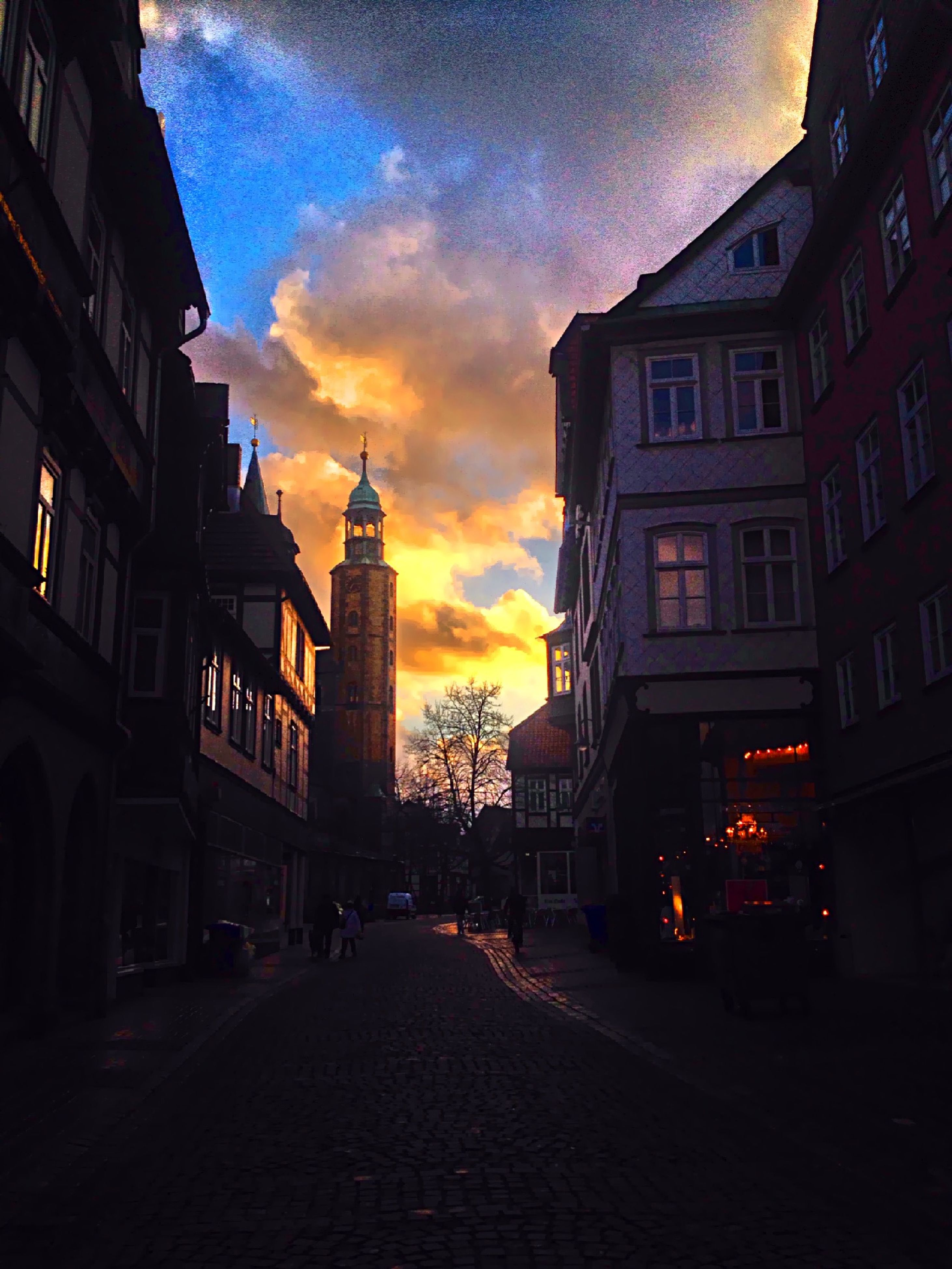 building exterior, architecture, built structure, sunset, city, sky, street, the way forward, residential building, building, transportation, road, cloud - sky, car, residential structure, orange color, city life, diminishing perspective, outdoors, city street