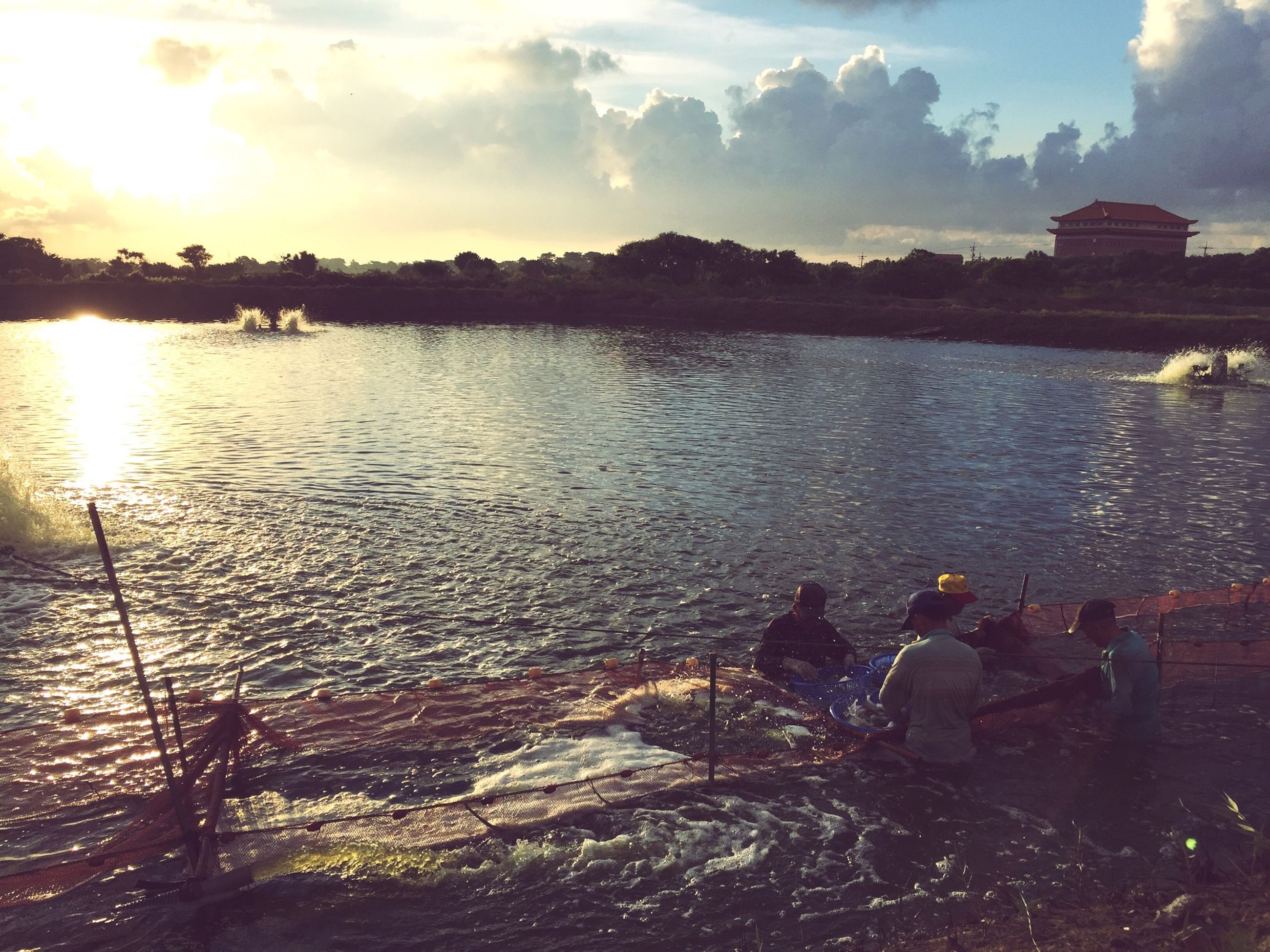 water, sky, lifestyles, leisure activity, sun, sunlight, sunset, reflection, men, cloud - sky, sea, sunbeam, nature, person, river, lake, beauty in nature, scenics, tranquility