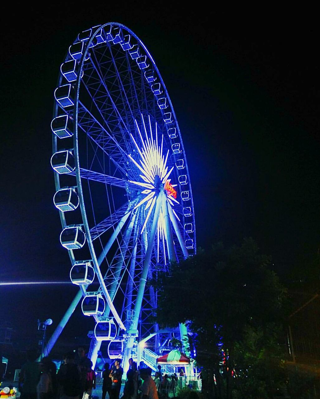 arts culture and entertainment, illuminated, night, ferris wheel, amusement park, nightlife, low angle view, leisure activity, amusement park ride, blue, multi colored, outdoors, sky, no people