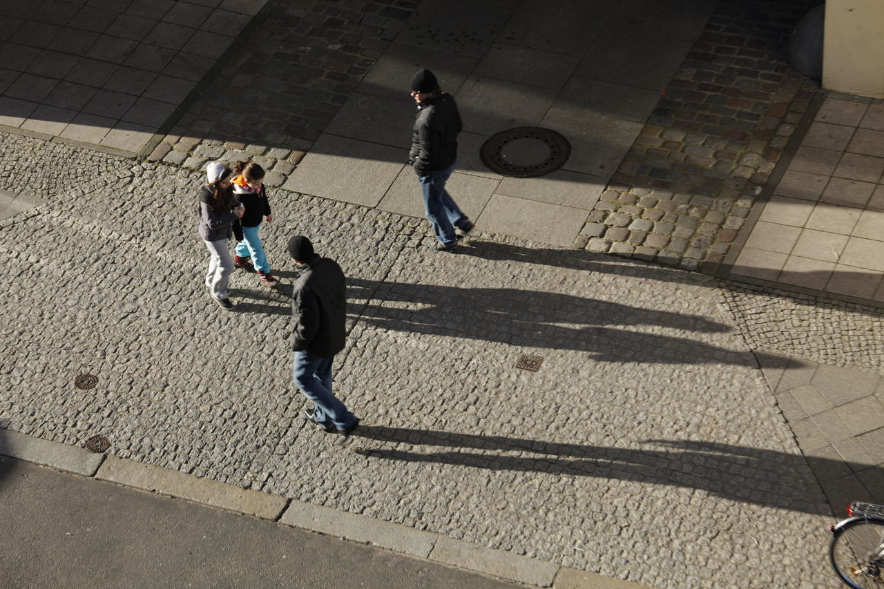 high angle view, real people, walking, full length, day, shadow, men, leisure activity, outdoors, lifestyles, two people, boys, city, adult, people