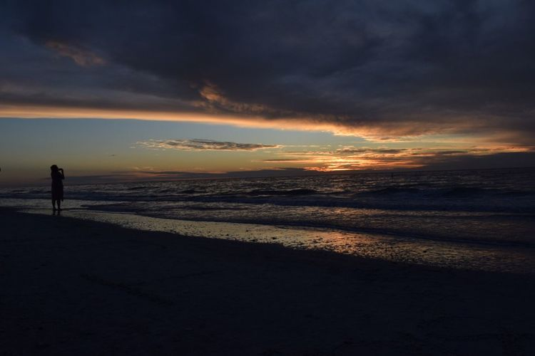 Sunset Beach Sea Nature Scenics Beauty In Nature Shore Sky Water Tranquil Scene Horizon Over Water Tranquility Silhouette Cloud - Sky Sand Standing One Person Outdoors Real People Vacations