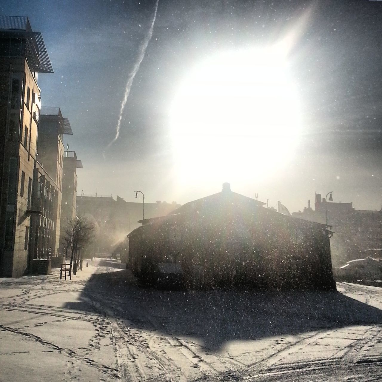 snow, winter, lens flare, cold temperature, sunlight, sunbeam, building exterior, sun, architecture, weather, outdoors, built structure, day, sky, nature, the way forward, no people, clear sky, city, beauty in nature