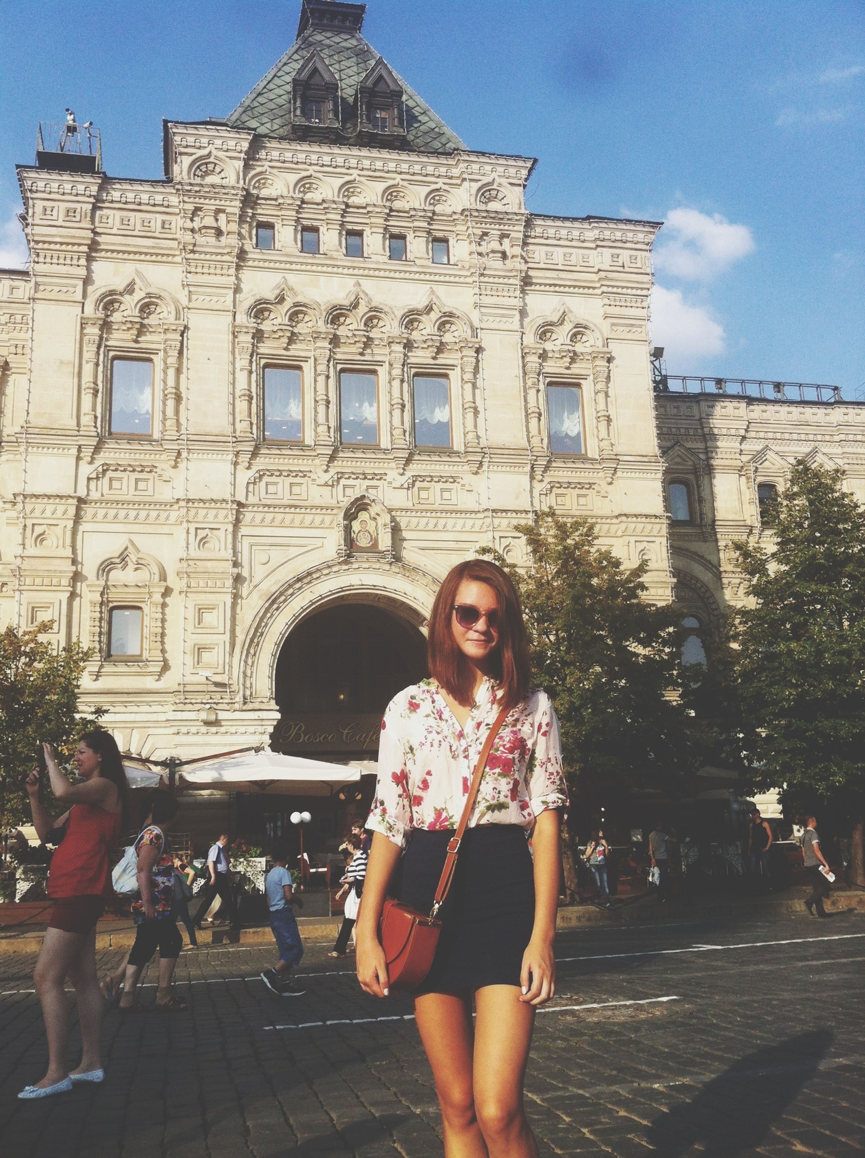 architecture, building exterior, built structure, lifestyles, leisure activity, person, young adult, casual clothing, standing, young women, front view, smiling, portrait, looking at camera, sky, full length, happiness, history