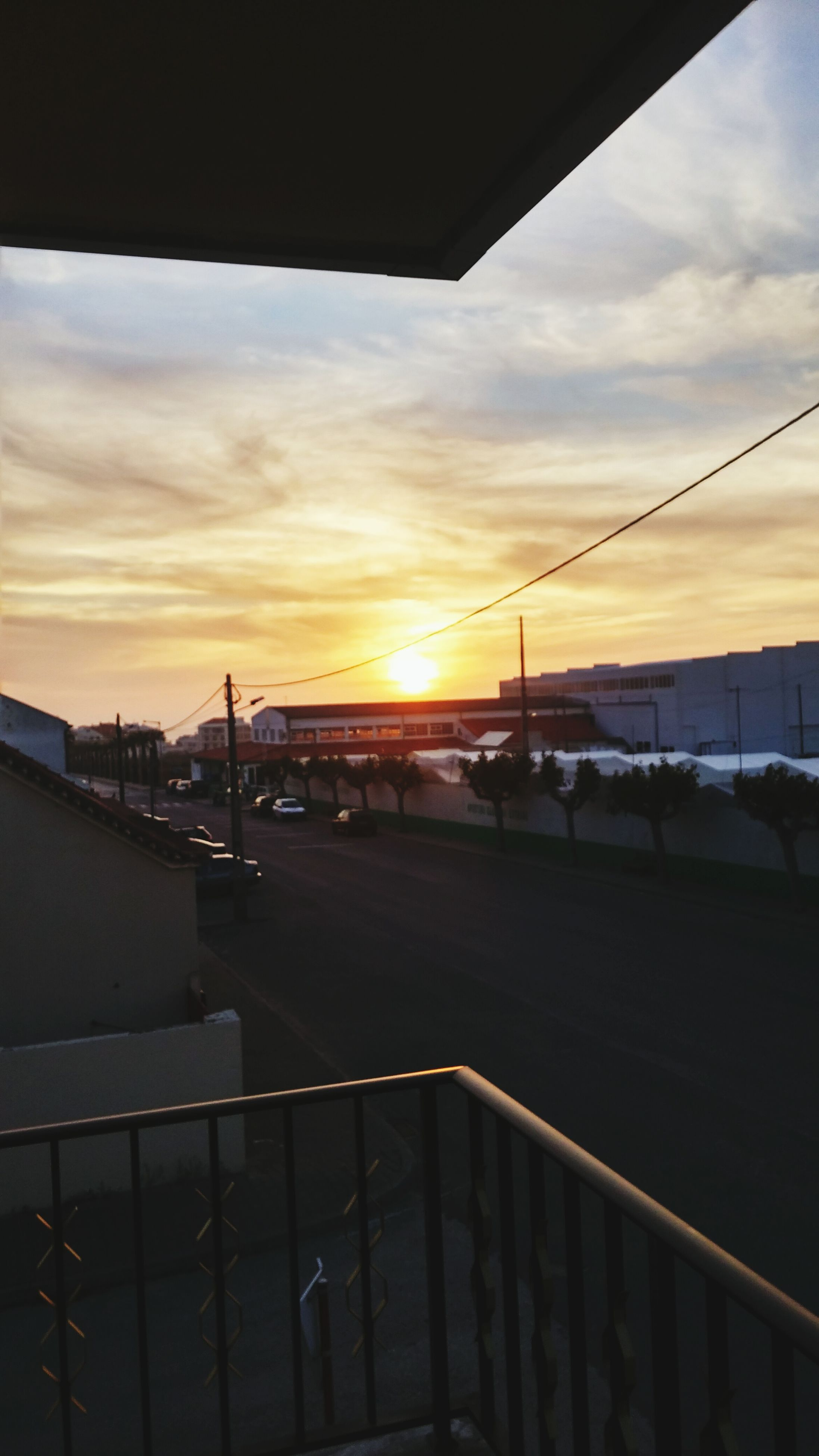 sunset, sky, sun, transportation, built structure, silhouette, cloud - sky, orange color, sunlight, railing, architecture, cloud, connection, street light, empty, outdoors, railroad station platform, the way forward, no people, bridge - man made structure