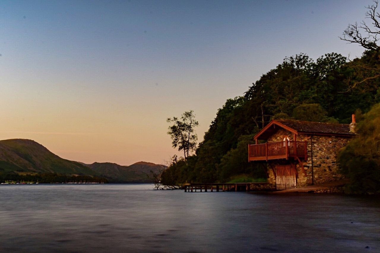 water, mountain, scenics, nature, tranquility, built structure, tree, beauty in nature, tranquil scene, architecture, no people, waterfront, sunset, outdoors, sea, sky, clear sky, building exterior, day