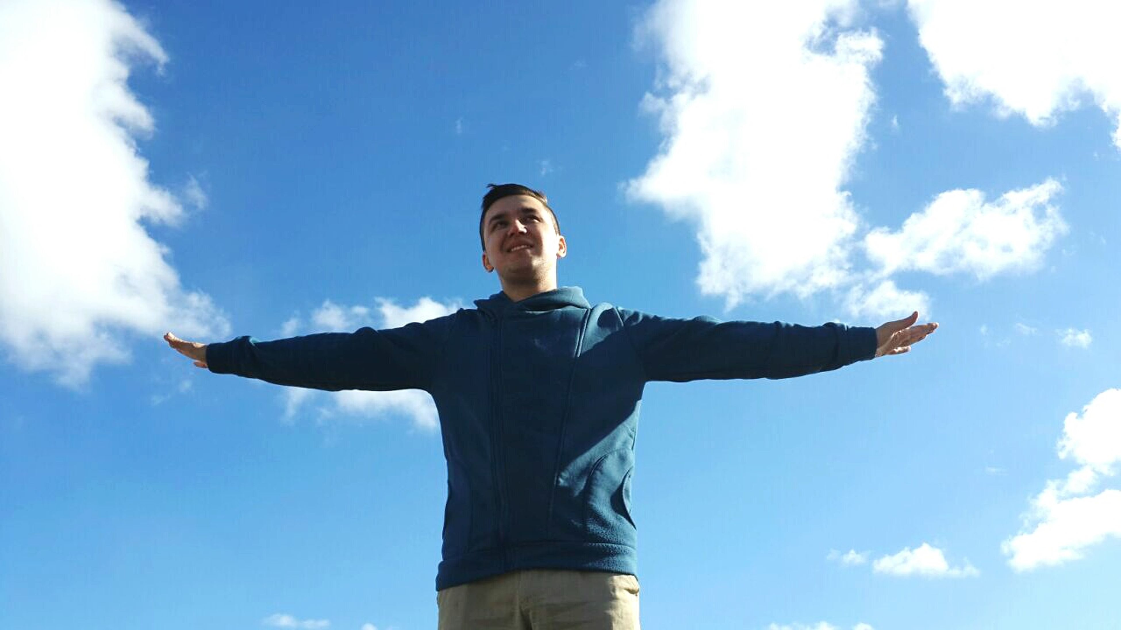 low angle view, sky, cloud - sky, blue, standing, cloud, portrait, young adult, looking at camera, human representation, casual clothing, lifestyles, day, cloudy, leisure activity, outdoors, front view, person