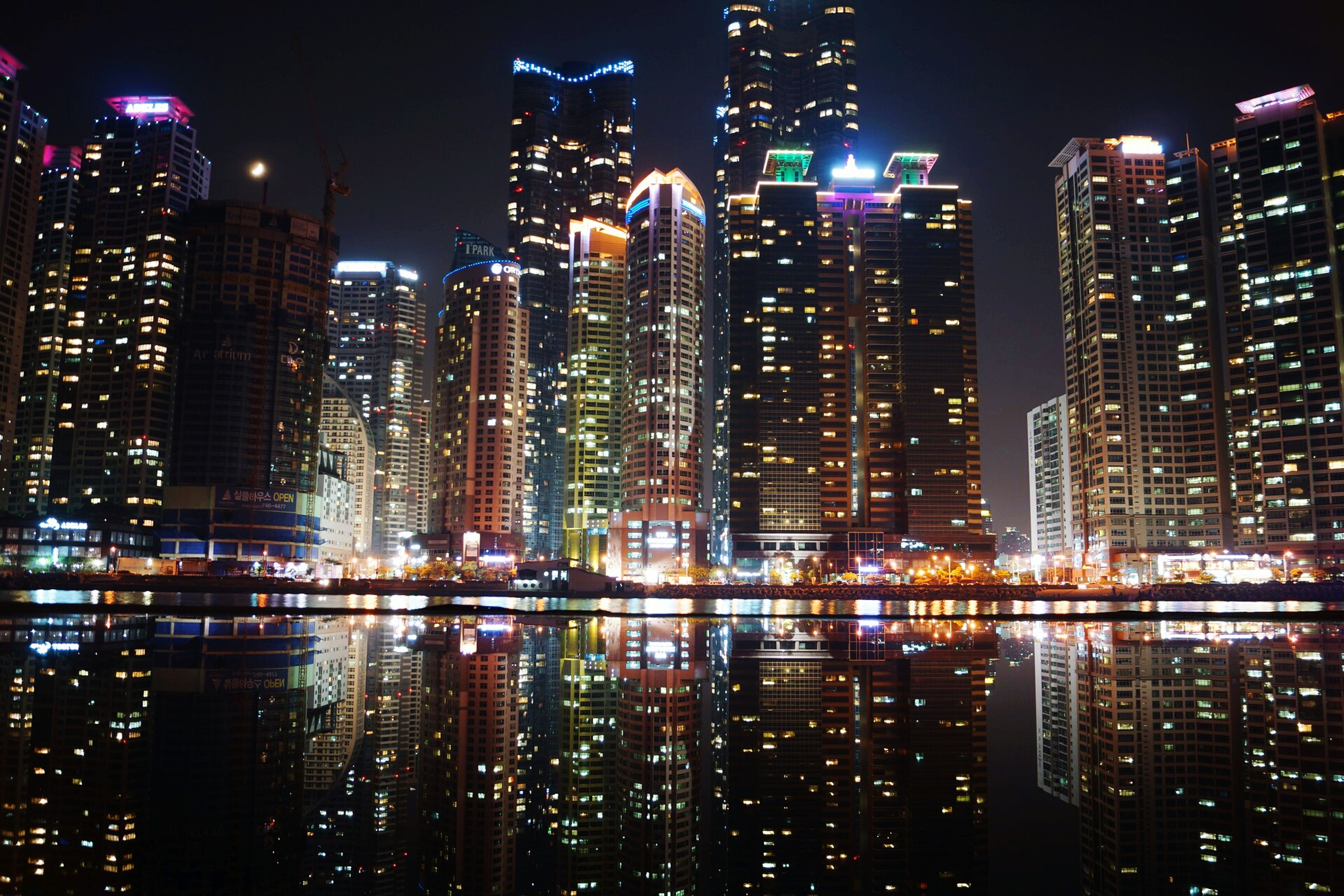 night, illuminated, building exterior, city, architecture, skyscraper, built structure, cityscape, modern, tall - high, tower, office building, financial district, urban skyline, capital cities, reflection, city life, crowded, travel destinations, tall