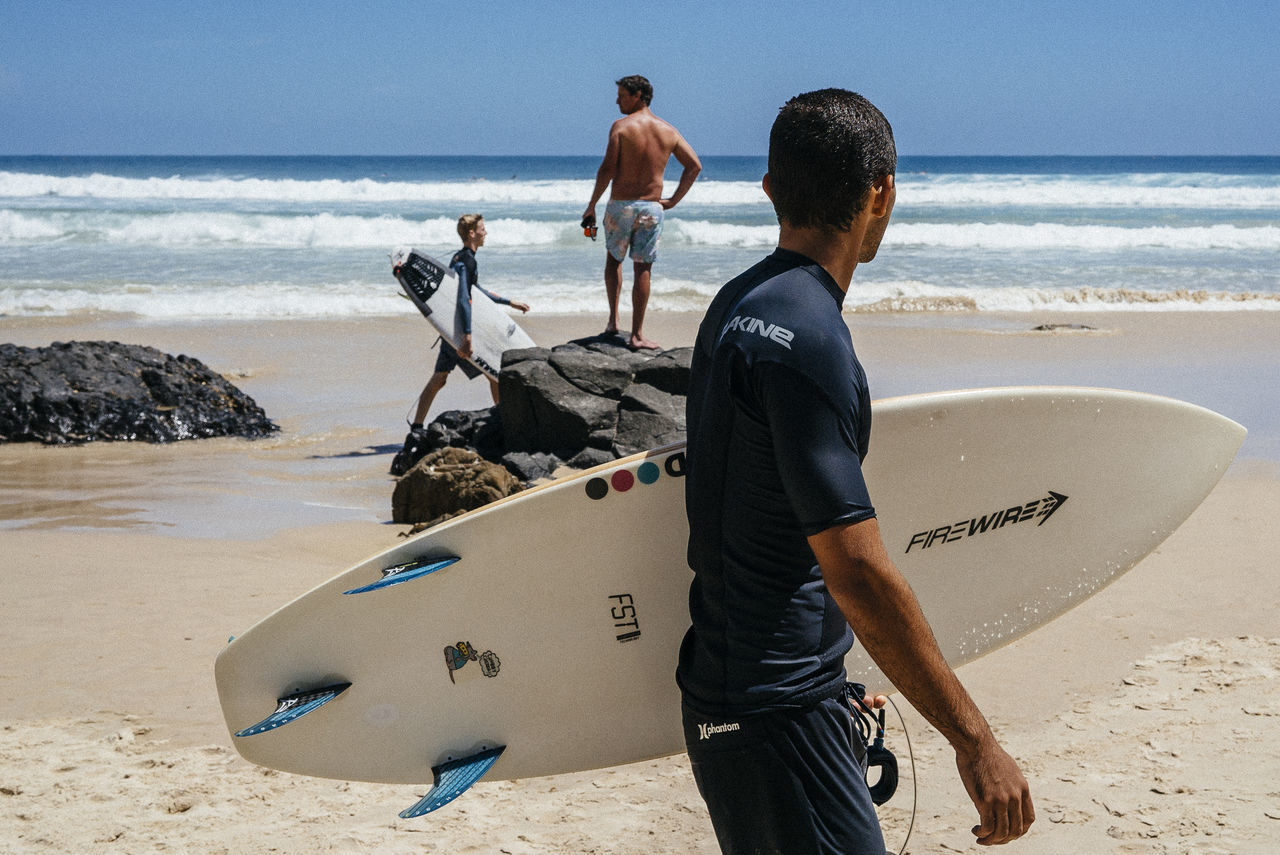 sea, beach, sand, real people, shore, shirtless, standing, surfboard, wave, horizon over water, day, men, text, leisure activity, water, surfing, outdoors, lifestyles, vacations, nature, full length, sky, boys, beauty in nature, one person, adult, people