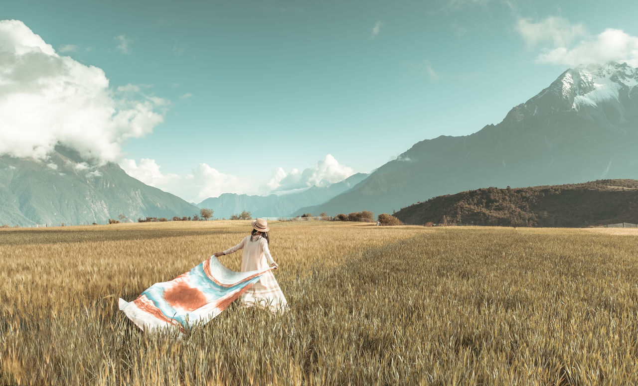 Girl On Field Against Mountains