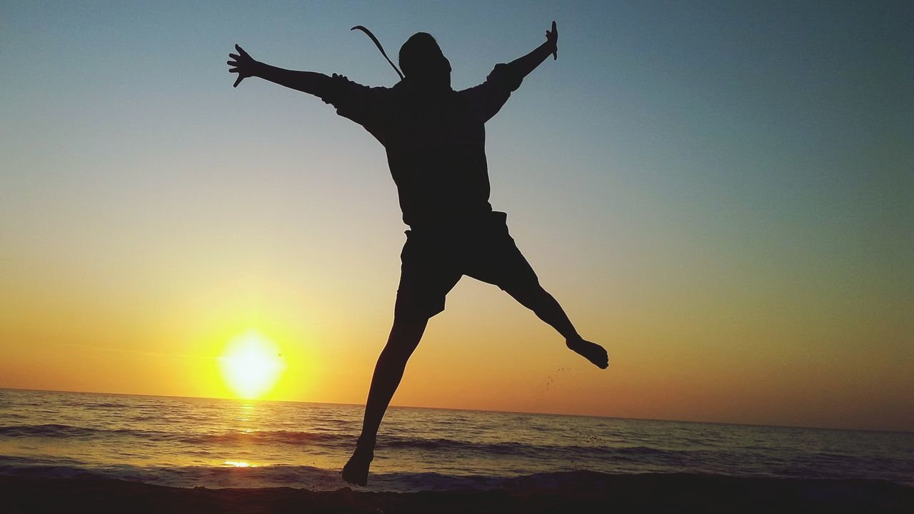 Silhouette Excited Man Jumping Over Beach During Sunset