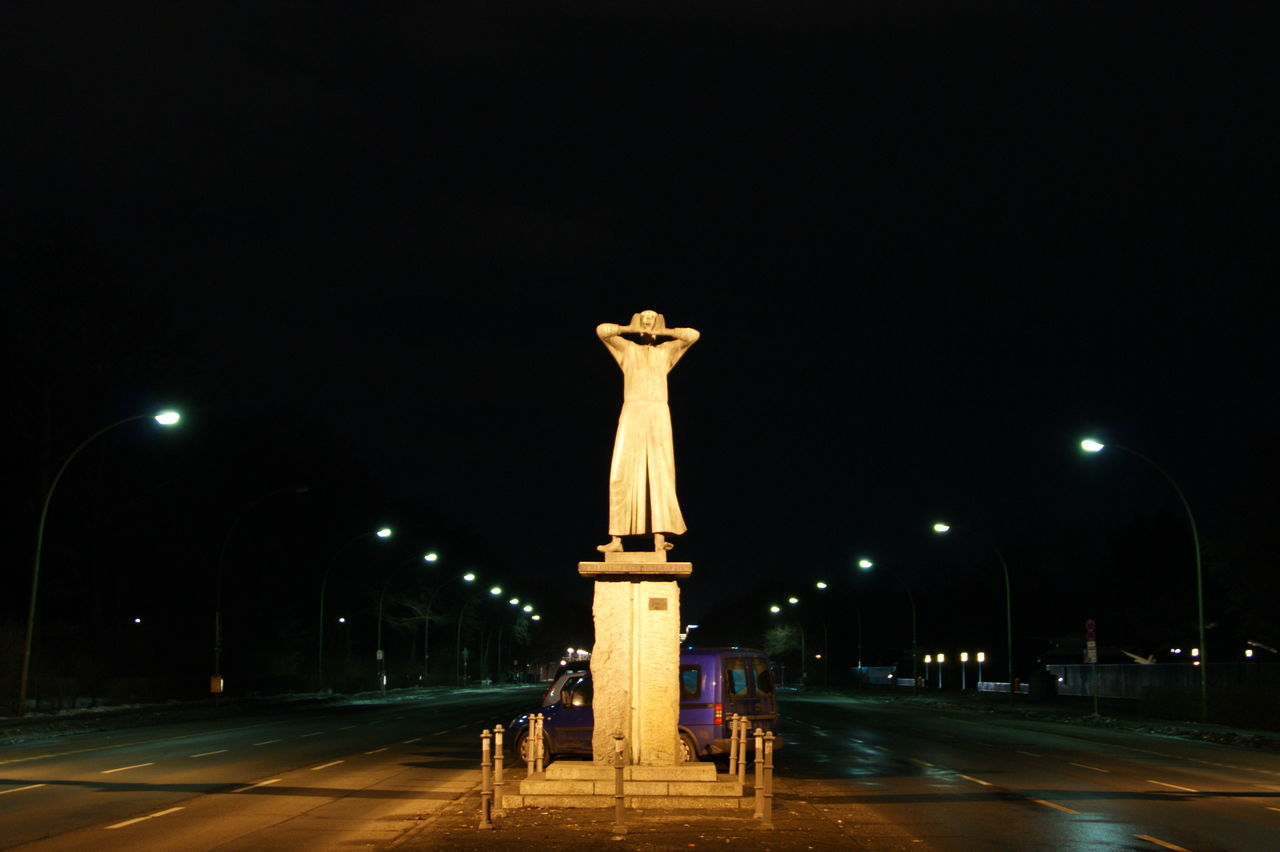 night, street light, statue, illuminated, sculpture, road, lighting equipment, monument, famous place, history, travel destinations, architectural column, sky, tourism, town square, outdoors, city life, victory column, culture, tall - high