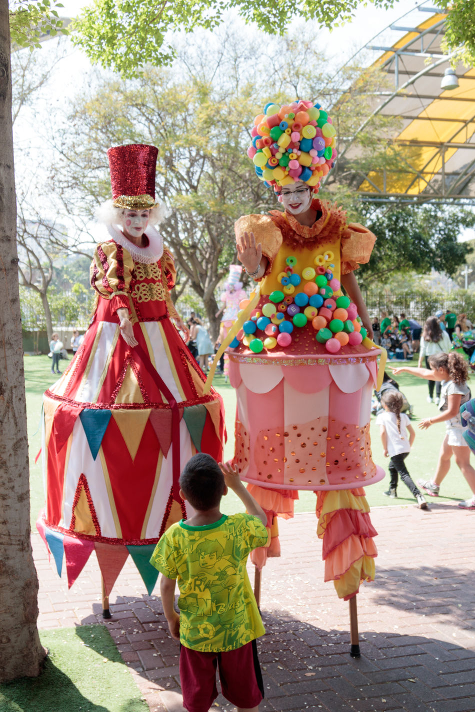 Tel Aviv, Israel, April 16, 2016 : Clowns on stilts greet a small visitor to the attractions park in Tel Aviv, Israel Amusement  Attraction Beautiful Carnival Clown Costume Day Entertainment Event Face Festival Fun Funny Happiness Happy Holiday Joy Light Outdoors Park People Performer  Romantic Smile Stilt