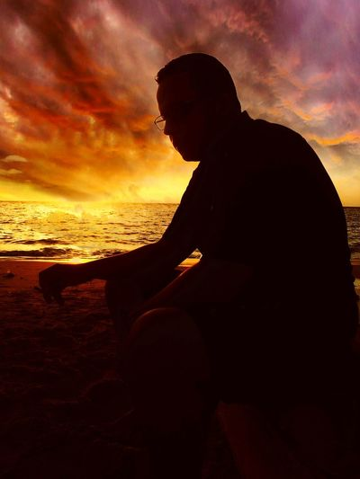 Sunset Silhouette One Man Only Cloud - Sky One Person Sky Adult Only Men Sea People Sitting Nature Relaxation Adults Only Side View Tranquility Horizon Over Water Beach Human Body Part Men Skyonfire Tranquility Silhouette Magicsky